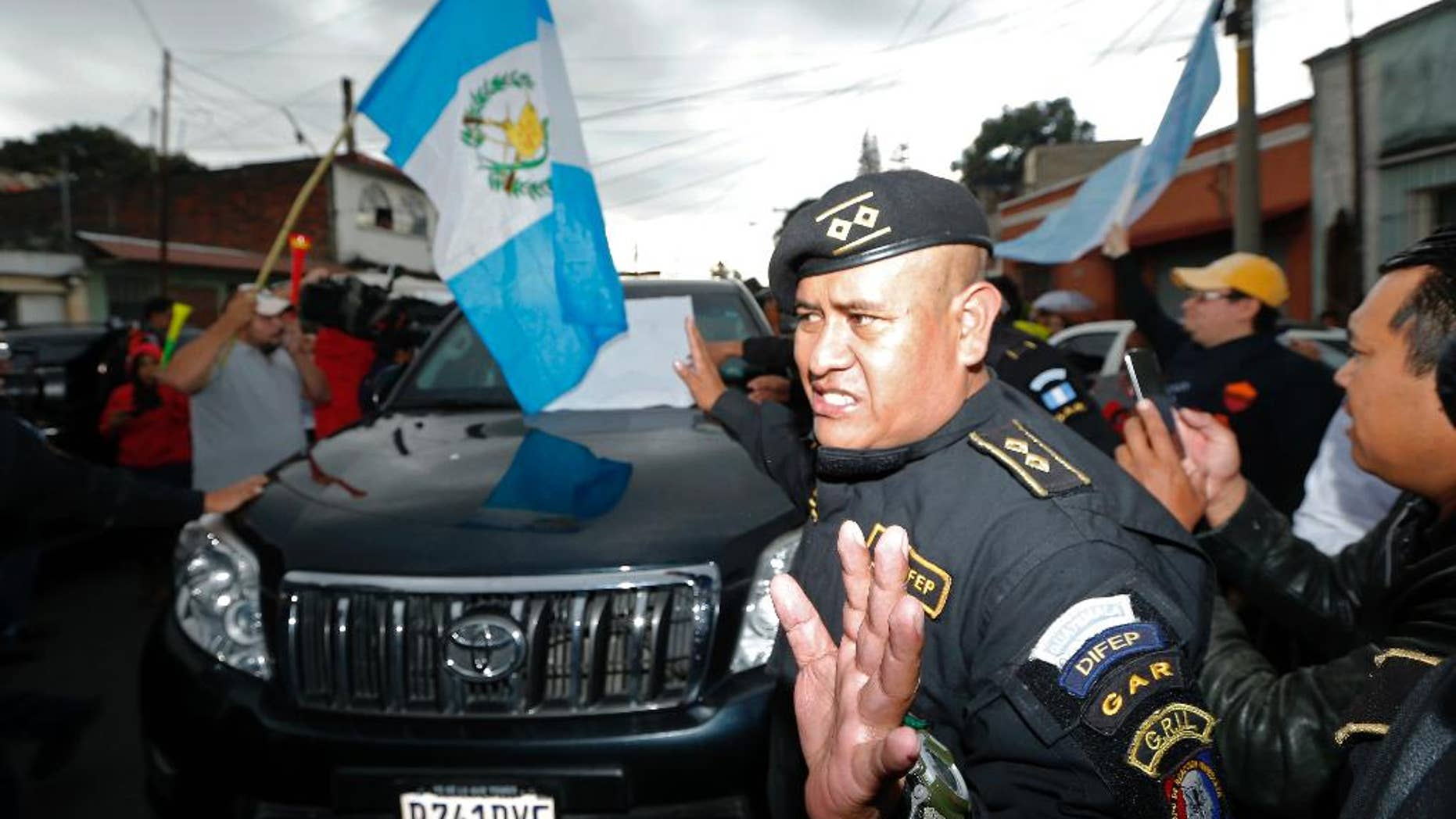 A Guatemalan police officer tries to clear a path for a vehicle carrying former President Otto Perez Molina, as he is transported to the Matamoros military barracks, in Guatemala City, Thursday, Sept 3, 2015. Perez Molina will spend the night in custody before a court hearing into corruption allegations against him reconvenes. He was taken from the court in an SUV and escorted by a dozen police vehicles, initially surrounded by a scrum of media cameras. (AP Photo/Moises Castillo)