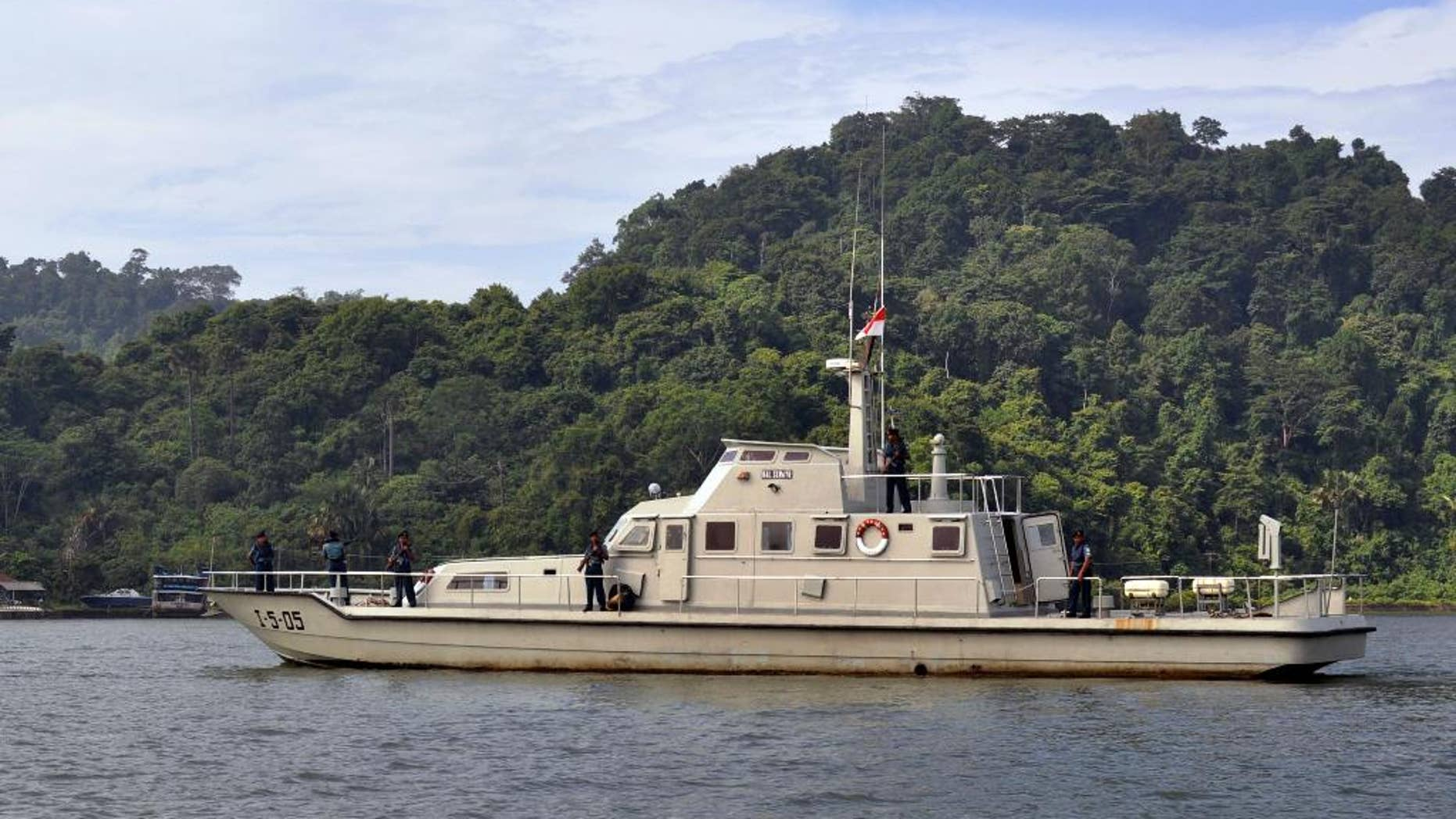 An Indonesian Navy boat carrying armed crew members patrol the waters near the prison island of Nusakambangan, background, where the planned executions of seven convicted foreign drug smugglers will be performed, in Cilacap, Central Java, Indonesia, Tuesday, Feb. 24, 2015. Indonesia is preparing the executions of the drug convicts from Australia, Brazil, France, Ghana, Nigeria and the Philippines. (AP Photo/Wagino)