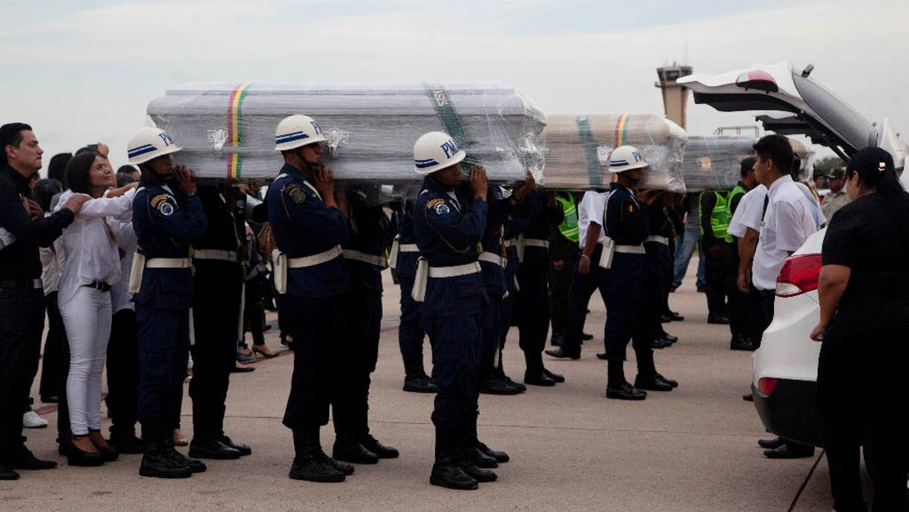 """Coffins carrying LaMia flight crew members who died in a plane crash are carried by soldiers to a hearse at the Viru Viru airport in Santa Cruz, Bolivia, Friday, Dec. 2, 2016. Victims of this week's tragic air crash in the Andes were flown home Friday as Bolivia's president called for """"drastic measures"""" against aviation officials who signed off on a flight plan that experts and even one of the charter airline's executives said should never have been attempted because of a possible fuel shortage. (AP Photo/Juan Karita)"""