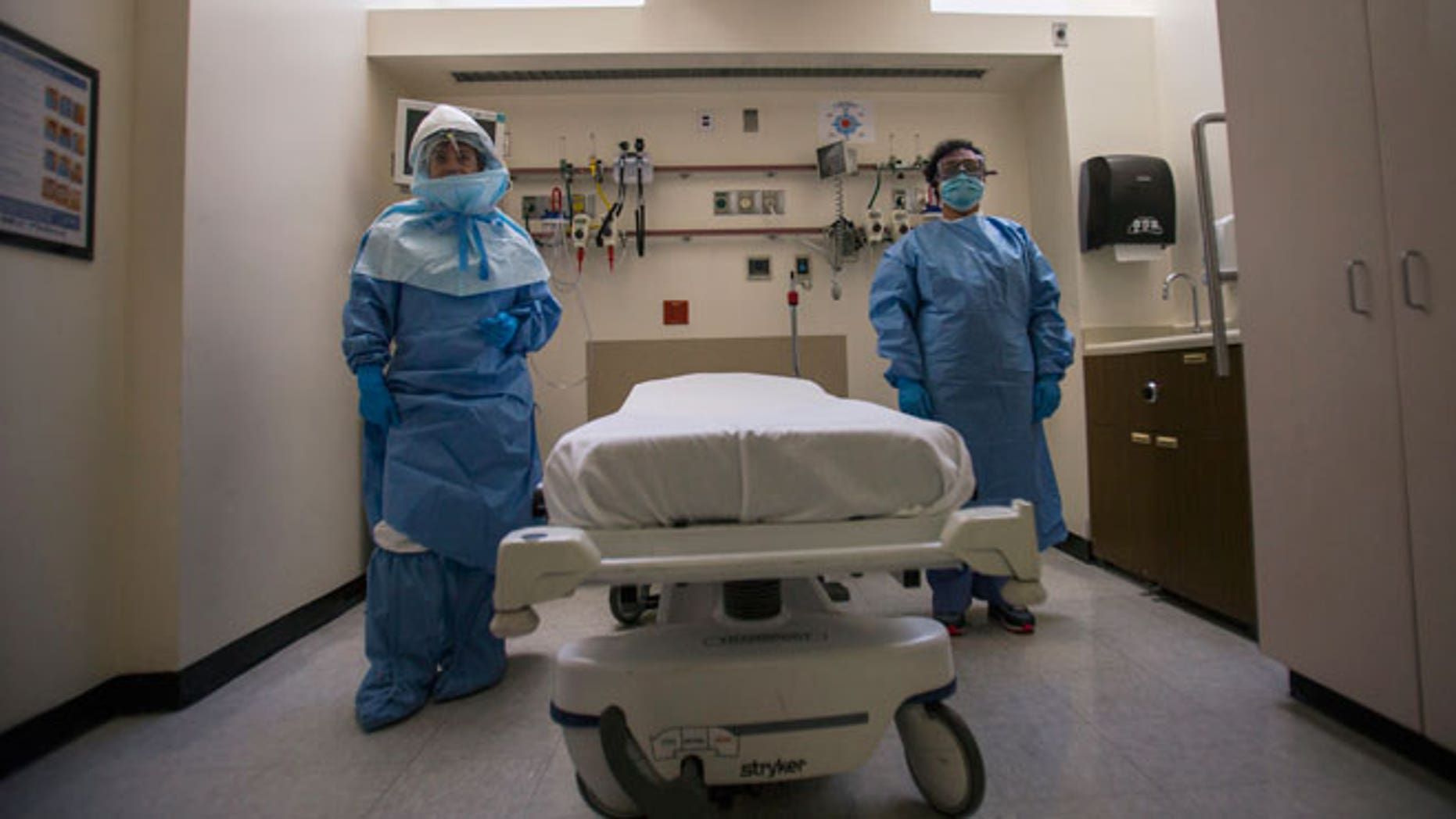 Health care workers display protective gear, which hospital staff would wear to protect them from an Ebola virus infection, inside an isolation room as part of a media tour in the emergency department of Bellevue Hospital in Manhattan, New York October 8, 2014.