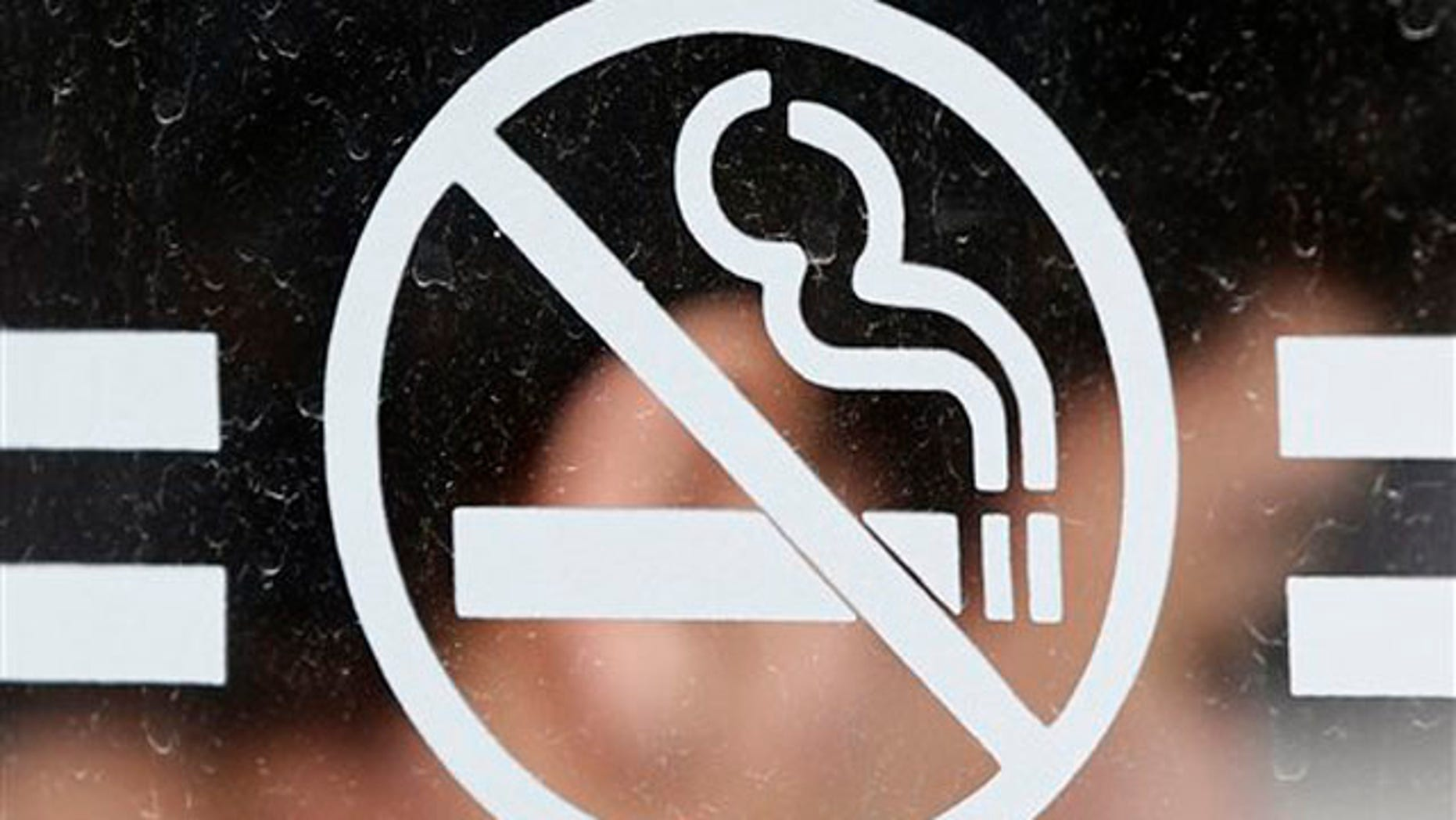 A student waits for a bus behind a no smoking sign at the State University of New York at Albany in Albany, N.Y., on Tuesday, June 26, 2012. Tobacco use bans are sweeping campuses nationwide. (AP Photo/Mike Groll)