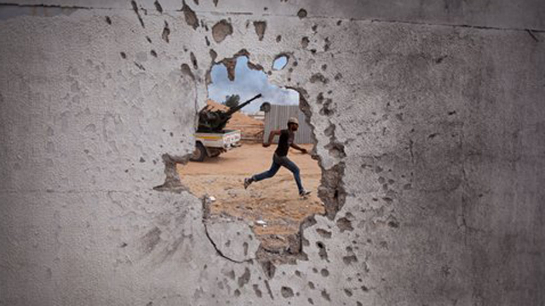 Oct. 7: A Libyan revolutionary fighter runs for cover while attacking pro-Qaddafi forces.