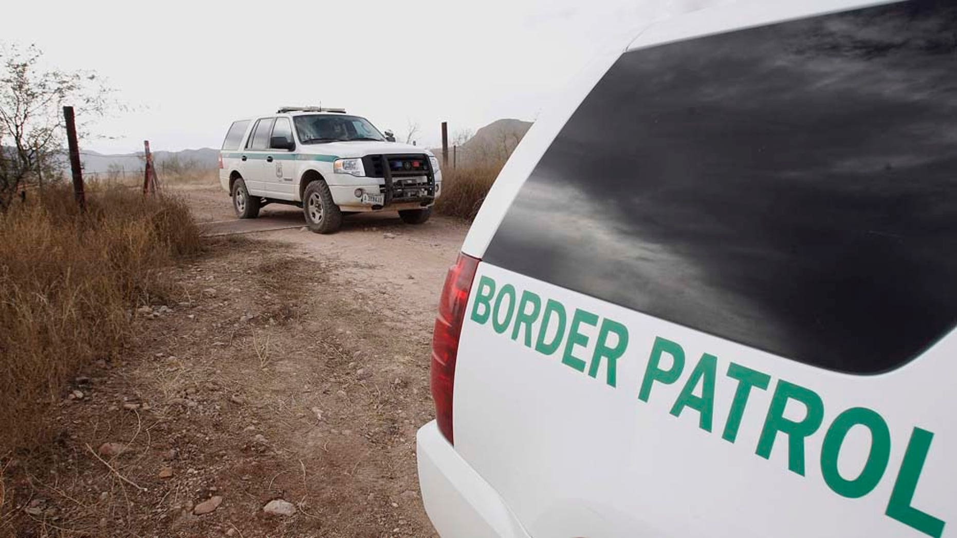 """FILE - In this Thursday, Dec. 16, 2010 file photo, U.S. Border Patrol vehicles come and go from a checkpoint, as teams of border officers comb through the Arizona desert about 10 miles north of Mexico in search of the lone outstanding suspect in the fatal shooting of Border Patrol agent Brian Terry in the rugged terrain in Rio Rico, Ariz.  The shooting Tuesday night came after agents spotted suspected bandits known for targeting illegal immigrants along a violent smuggling corridor. State Sen. Steve Smith, R-Maricopa, was the sponsor of a bill that was signed into law recently that will use donated money and inmate labor to build a """"secure fence"""" along the U.S.-Mexico border. (AP Photo/Ross D. Franklin, file)"""