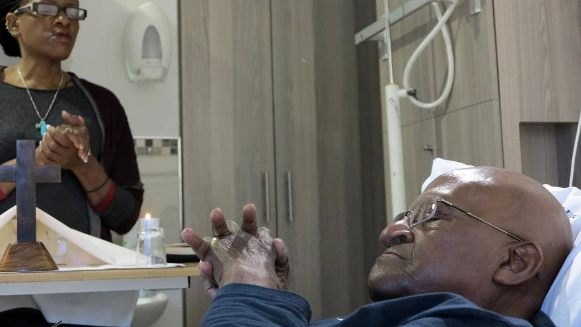 In this photo provided by Oryx Media shows retired Anglican Archbishop Desmond Tutu, praying in his hospital bed in Cape Town, South Africa Tuesday Aug. 4, 2015. Tutu left the hospital after being treated for an infection there since last month, his foundation said.  (Benny Gool/Oryx Media via AP) CREDIT MANDATORY