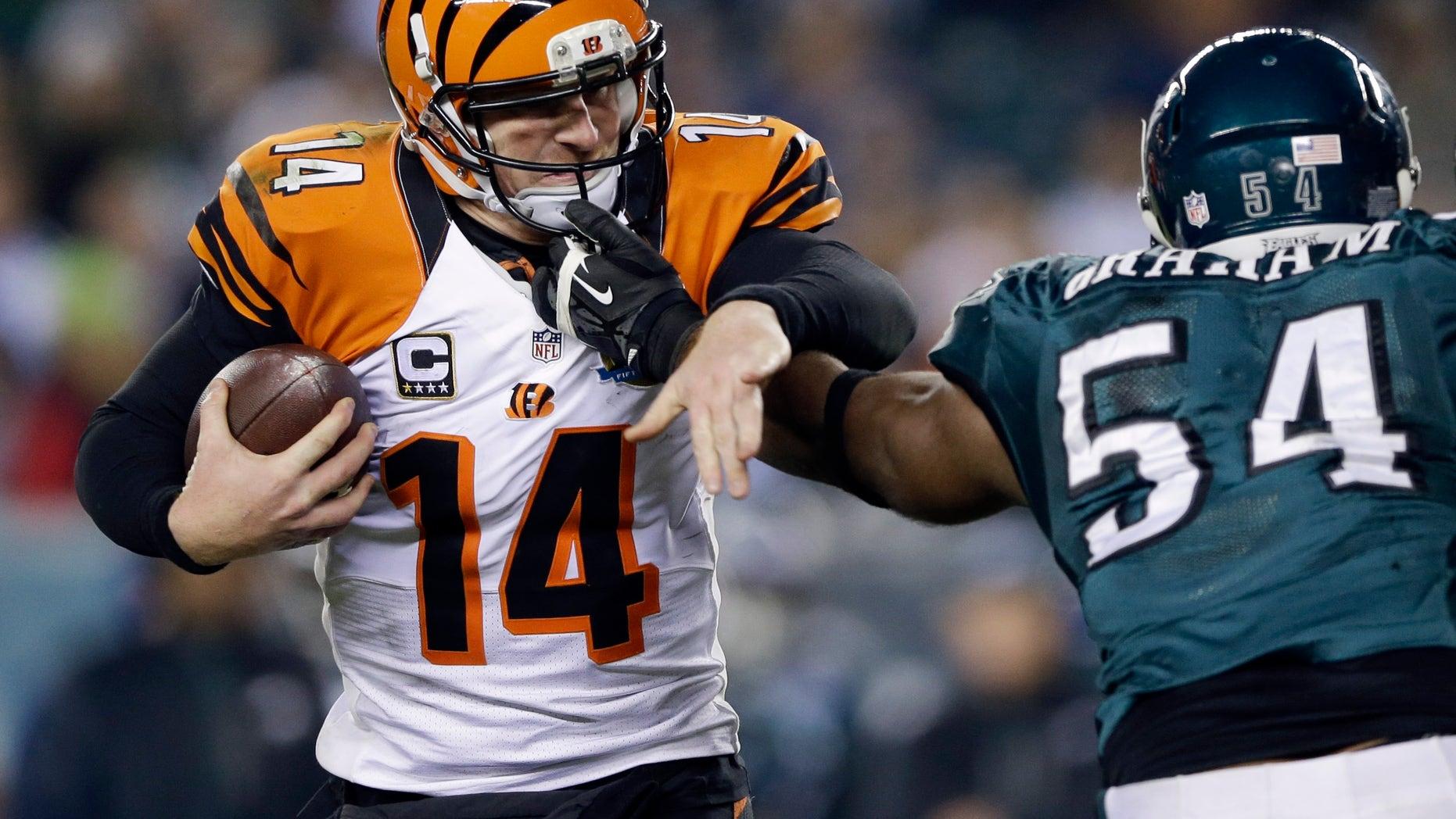 Cincinnati Bengals' Andy Dalton, left, tries to break free from Philadelphia Eagles' Brandon Graham in the second half of an NFL football game, Thursday, Dec. 13, 2012, in Philadelphia. (AP Photo/Matt Rourke)