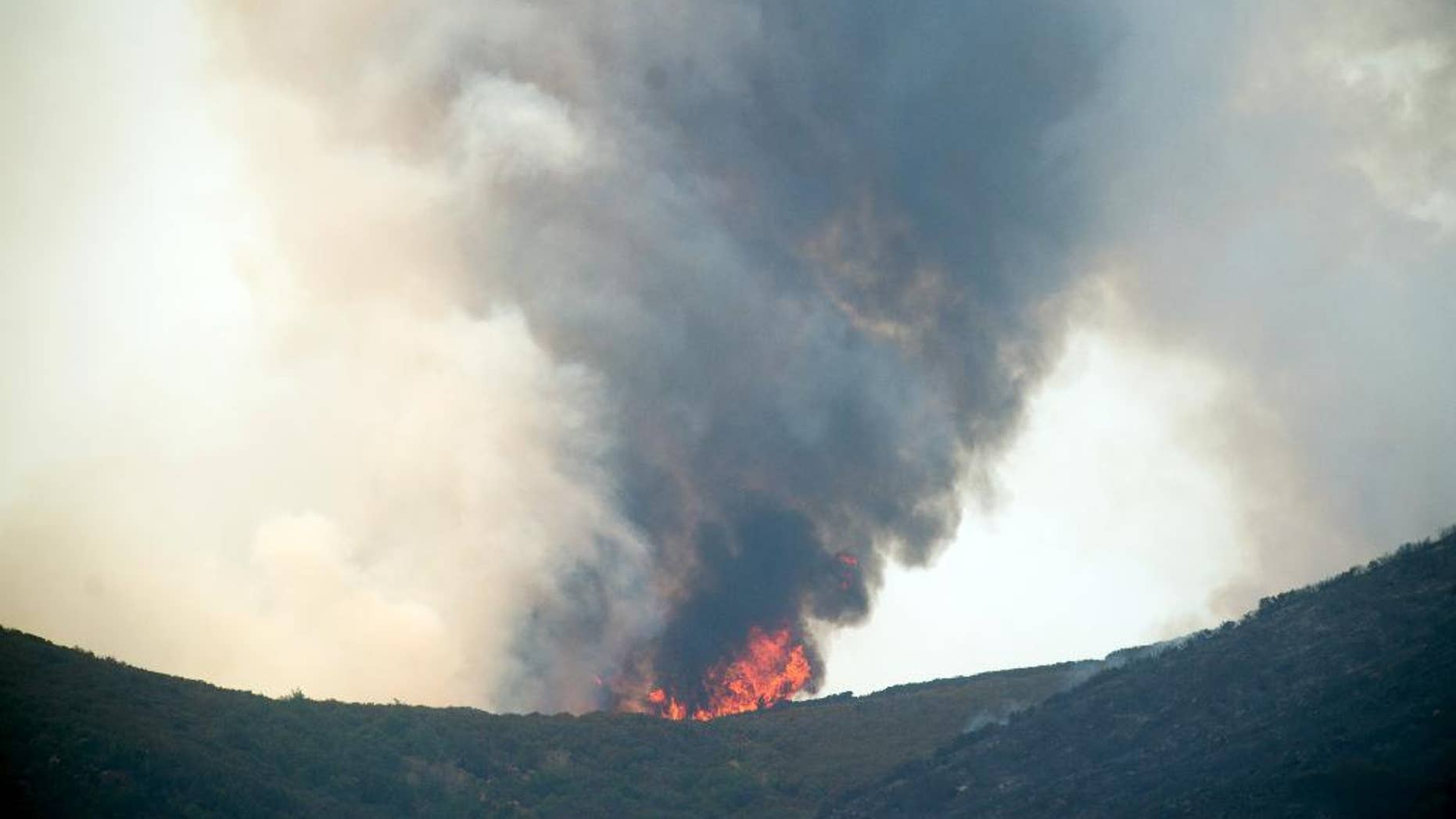 Smoke and flames rise from a ridge top as the Wragg fire burns near Winters, Calif., on Thursday, July 23, 2015. According to Cal Fire, the blaze scorched more than 6,000 acres and is threatening 200 structures. (AP Photo/Noah Berger)