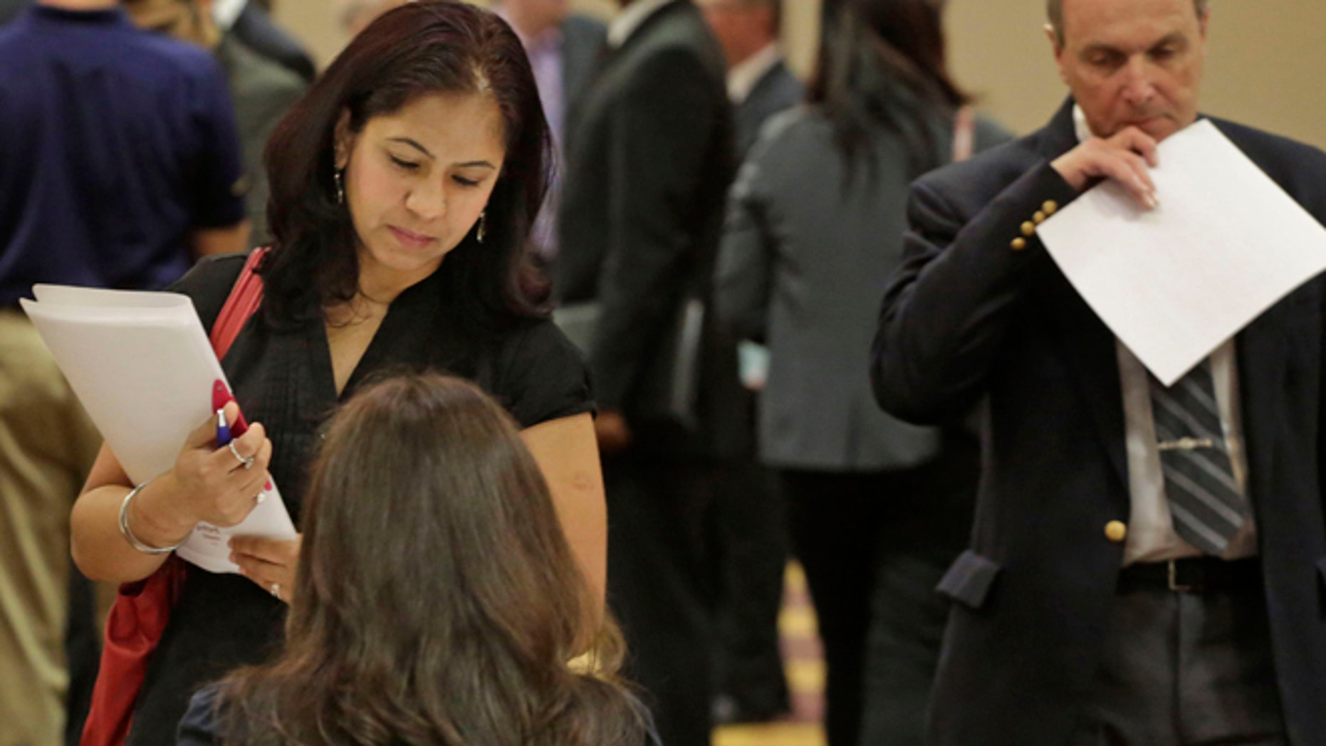 In this May 29, 2013 photo, job seeker Anu Vatal of Chicago, speaks with Patrice Tosi of BluePay, seated, during a career fair in Rolling Meadows, Ill. The U.S. economy added 175,000 jobs in May, a gain that shows employers are hiring at a still-modest but steady pace despite government spending cuts and higher taxes, according to the Labor Department, Friday, June 7, 2013. (AP Photo/M. Spencer Green)