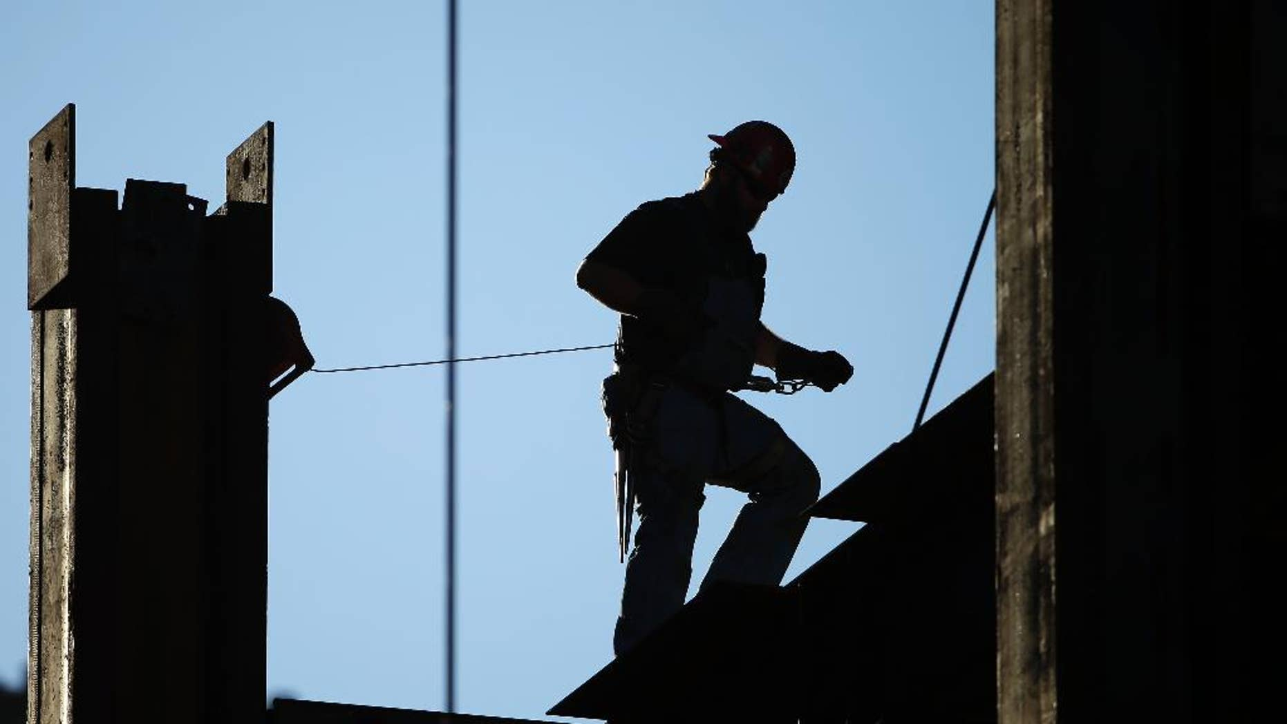 FILE - In this Sept. 15, 2015, file photo, an iron worker works on the new Comcast Innovation and Technology Center under construction, in Philadelphia. The Commerce Department reports on U.S. construction spending in November, on Monday, Jan. 4, 2016. (AP Photo/Matt Rourke, File)