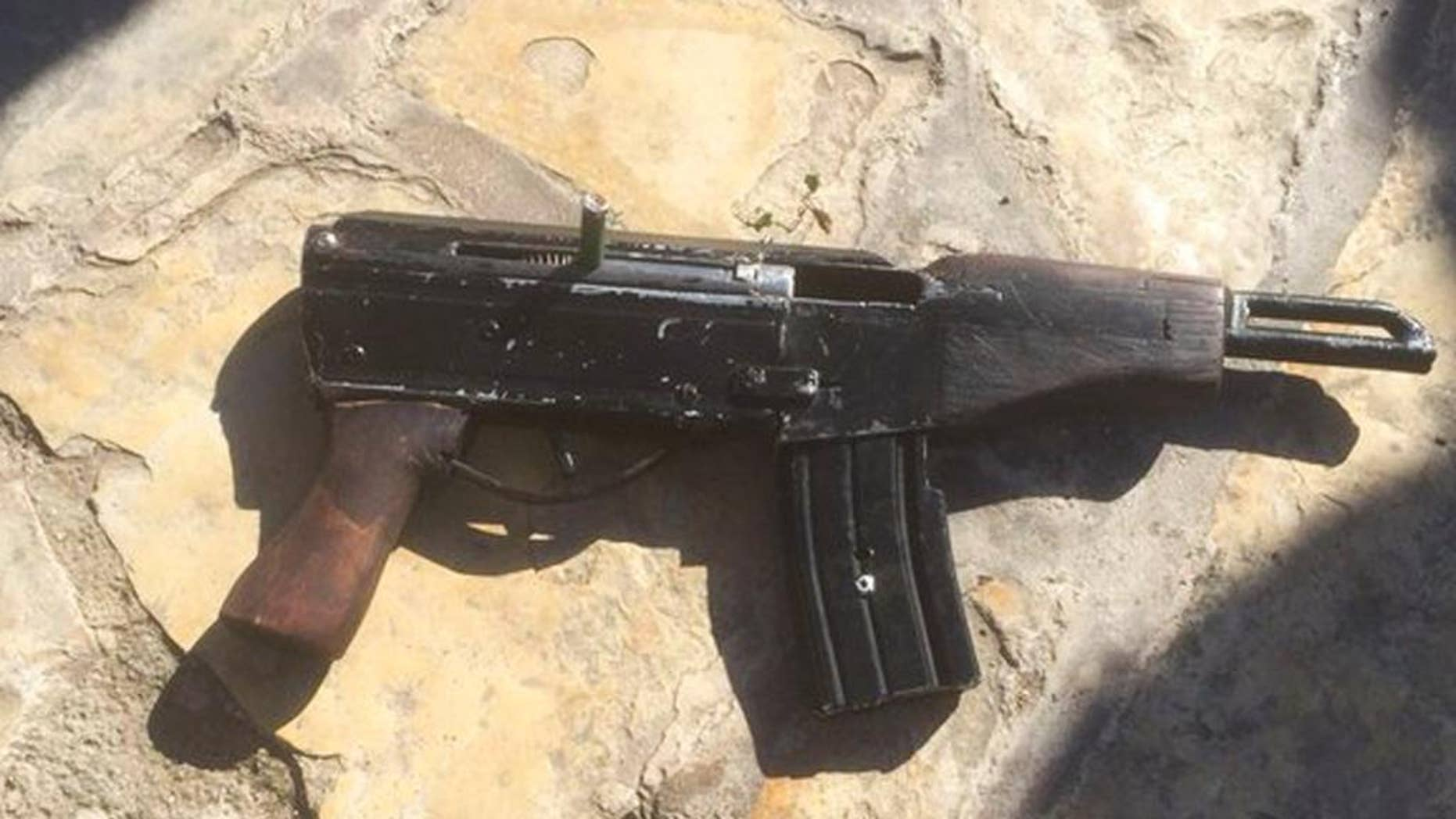 """This undated photo provided by the Israeli Police shows a handmade gun produced in the West Bank. Welded together from spare gun parts and pipes, the gun looks like a handgun but with an extended barrel and a long magazine of bullets. The weapon, known by its street name """"Carlo,"""" was used by Palestinian gunmen to kill four people and wound five others in Tel Aviv on Wednesday night as well as several other attacks since the current round of violence erupted in September. (Israeli Police via AP)"""