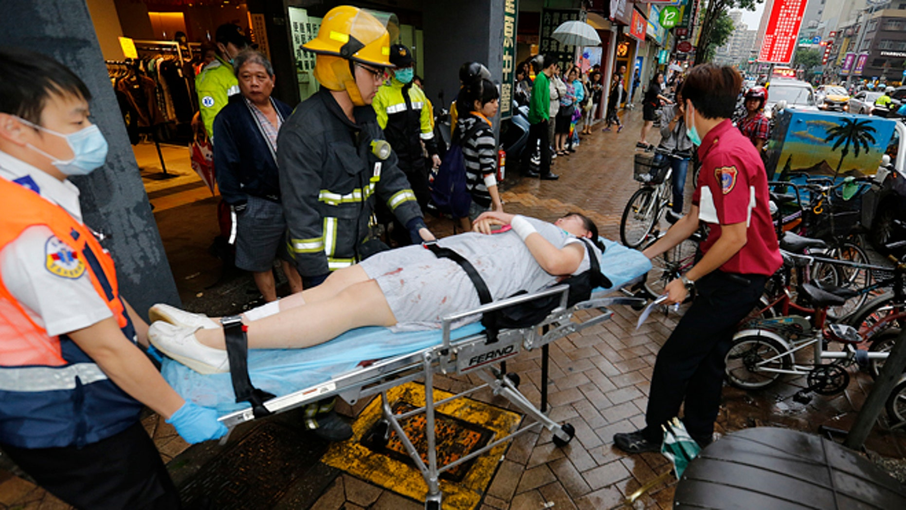 May 21, 2014: Paramedics remove a victim from a subway station exit after a knife attack on a subway in Taipei, Taiwan. (AP)