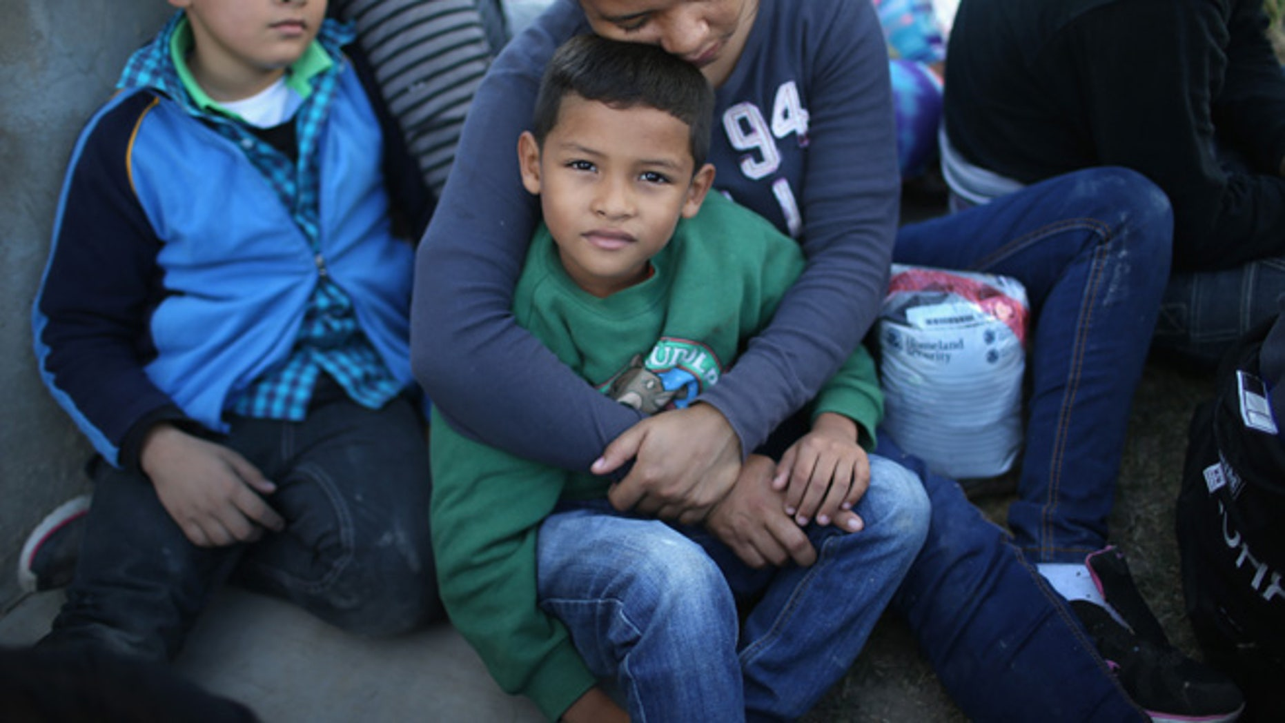 RIO GRANDE CITY, TX - DECEMBER 08:  A Honduran mother holds her son, 7, after she turned her family in to U.S. Border Patrol agents on December 8, 2015 near Rio Grande City, Texas. They had just illegally crossed the U.S.-Mexico border into Texas. She said she brought her two daughters to escape violence in the Central American country. The number of migrant families and unaccompanied minors has again surged in recent months, even as the total number of illegal crossings nationwide has gone down over the previous year.  (Photo by John Moore/Getty Images)