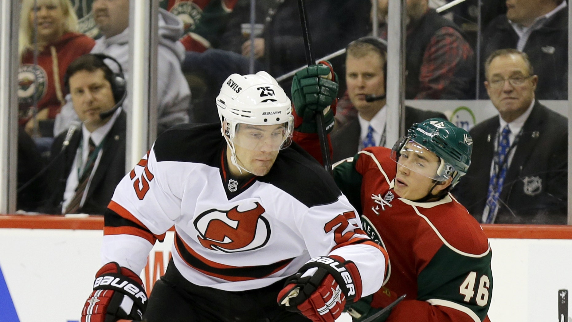 New Jersey Devils center Rostislav Olesz (25), of Czech Republic, and Minnesota Wild defenseman Jared Spurgeon get tangled as they battle for the puck during the second period of an NHL hockey game in St. Paul, Minn., Sunday, Nov. 3, 2013. (AP Photo/Ann Heisenfelt)