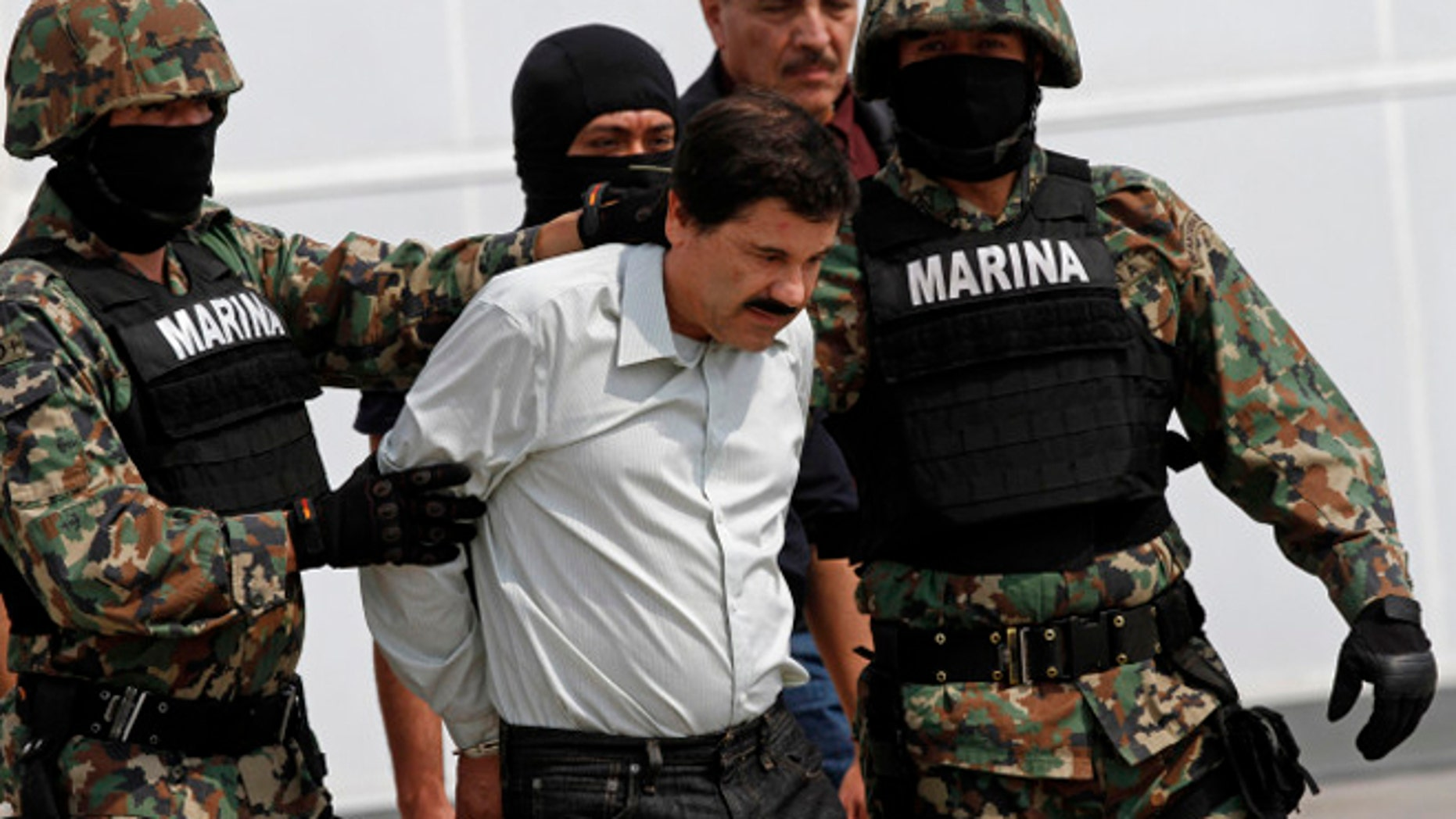 """Joaquin """"El Chapo"""" Guzman is escorted to a helicopter in handcuffs by Mexican navy marines at a navy hanger in Mexico City, Saturday, Feb. 22, 2014. A senior U.S. law enforcement official said Saturday, that Guzman, the head of MexicoÃs Sinaloa Cartel, was captured alive overnight in the beach resort town of Mazatlan. Guzman faces multiple federal drug trafficking indictments in the U.S. and is on the Drug Enforcement AdministrationÃs most-wanted list. (AP Photo/Marco Ugarte)"""