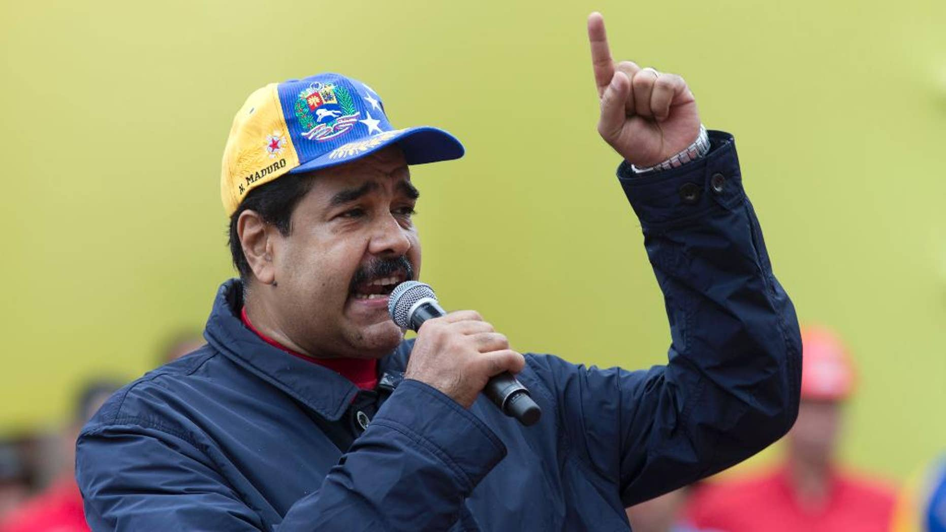 Venezuela's President Nicolas Maduro speaks during a May Day march in Caracas, Venezuela, Sunday, May 1, 2016. President Maduro ordered a 30 percent increase in the minimum wage, the latest move by the socialist government to grapple with high inflation and economic stagnation. (AP Photo/Ariana Cubillos)
