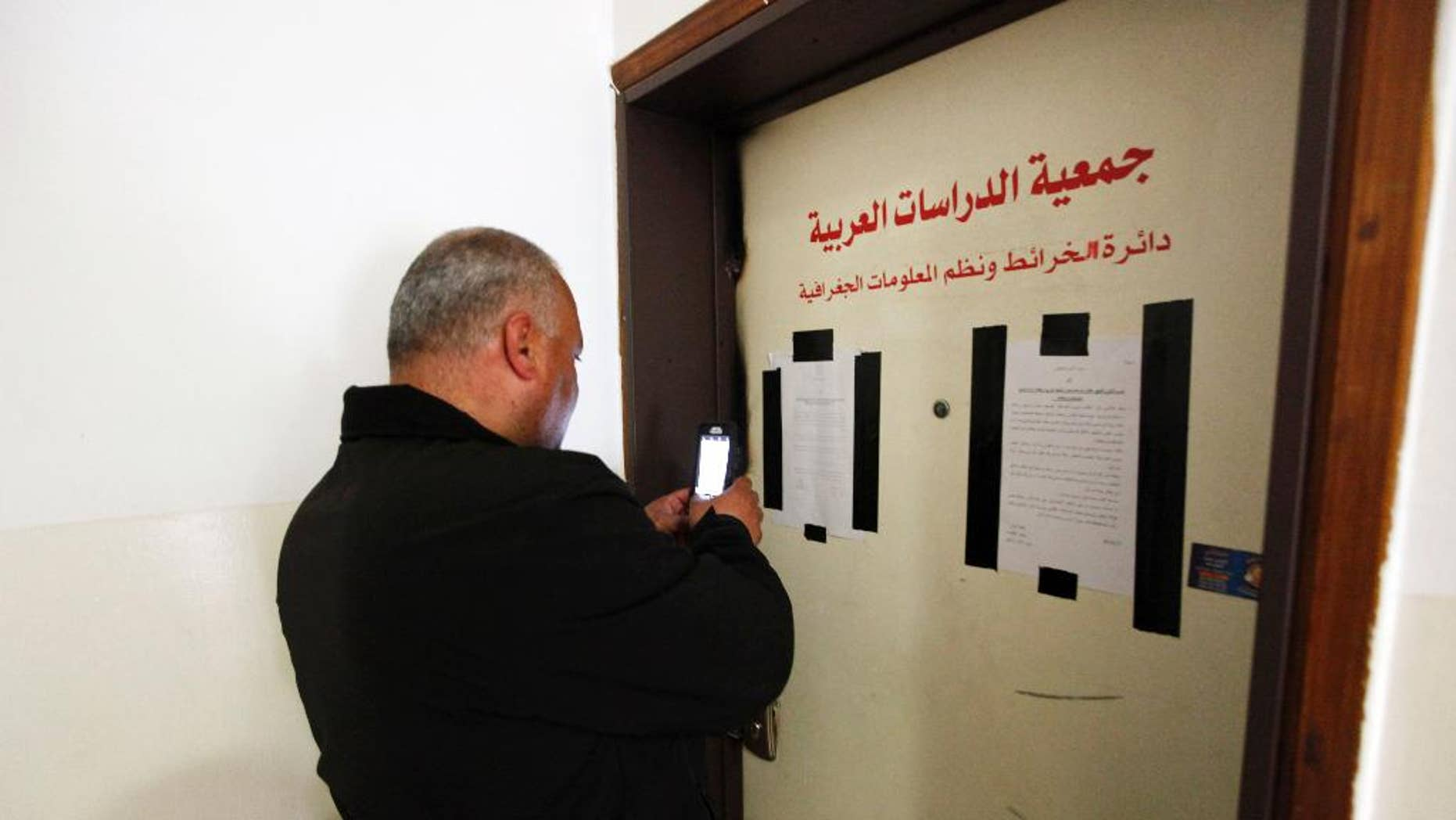 A man takes a photo of the sealed offices of Khalil Tufagji, a prominent Palestinian cartographer, in east Jerusalem, Tuesday, March 14, 2017. Israeli police have raided Tufagji's  office accusing him of working illegally on behalf of the Palestinian Authority. In a statement, police accused Tufagji of conducting research for the Palestinian Authority, including gathering information on Israeli development of east Jerusalem. His office is to remain closed for six months. (AP Photo/Mahmoud Illean)