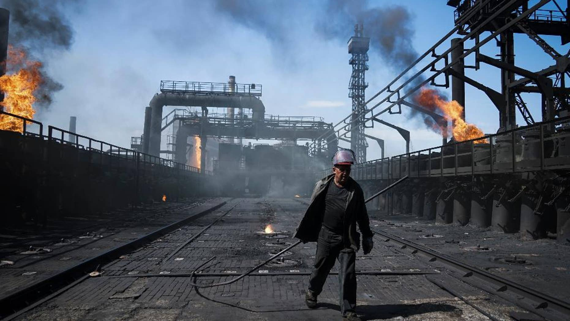 A worker carries a metal rod at the front-line Avdivka coking plant in eastern Ukraine, where the power cut out after shelling.