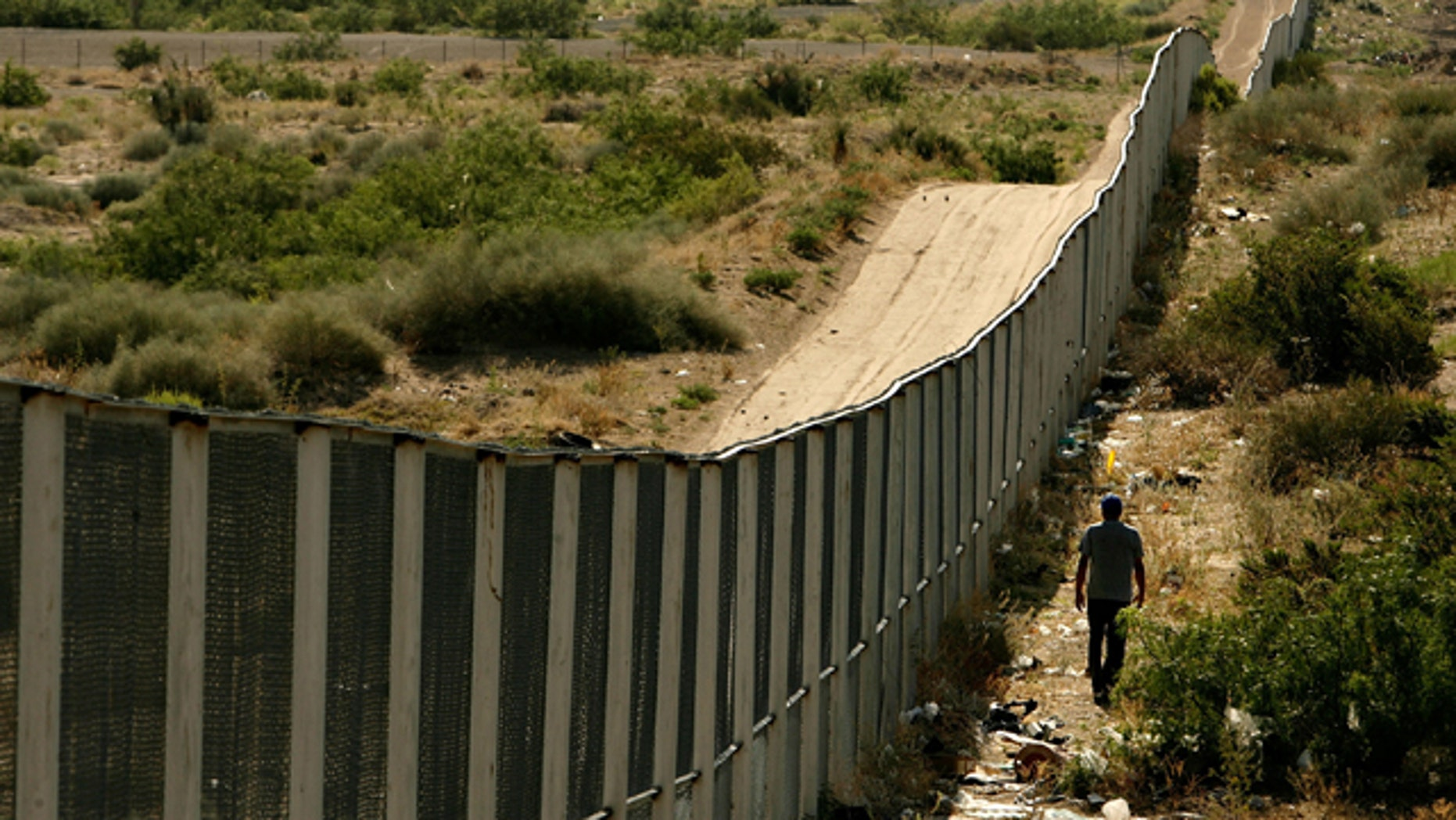 CIUDAD JUAREZ, CHIHUAHUA - JUNE 29:  A man walks along the border fence between the U.S. and Mexico on June 29, 2007 in the Anapra area of Ciudad Juarez, Mexico. This area is a popular crossing spot for immigrants to ilegally cross into the United States because houses are close to the border on the south side and the highway is close to the north side.  (Photo by Chip Somodevilla/Getty Images)