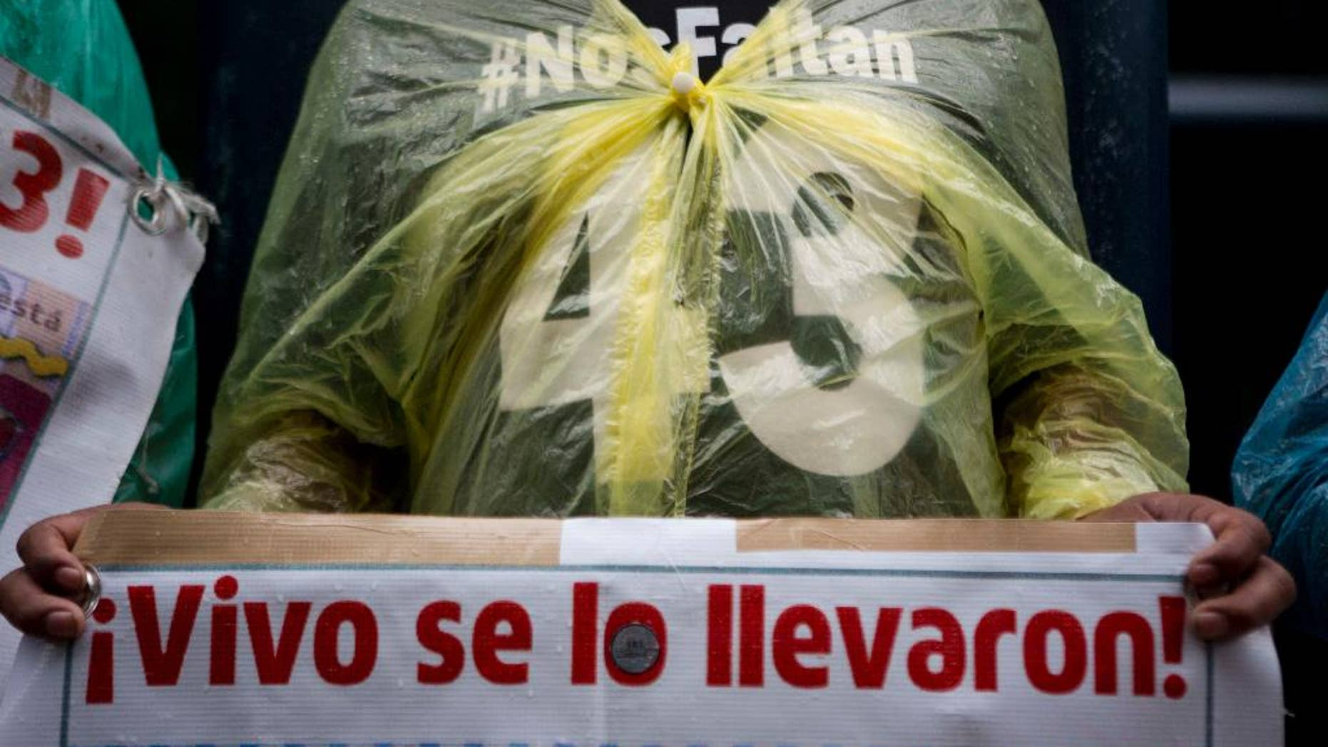 """FILE - In this May 26, 2016, file photo, a relative carries signs that reads in Spanish """"They took them alive!"""" referring to the 43 missing students from a rural teachers college during a march in Mexico City, Thursday. Mexico's National Human Rights Commission said Monday, July 11, that a classmate of 43 college students who disappeared in 2014 had been tortured before his body was found the following day.  (AP Photo/Eduardo Verdugo, File)"""
