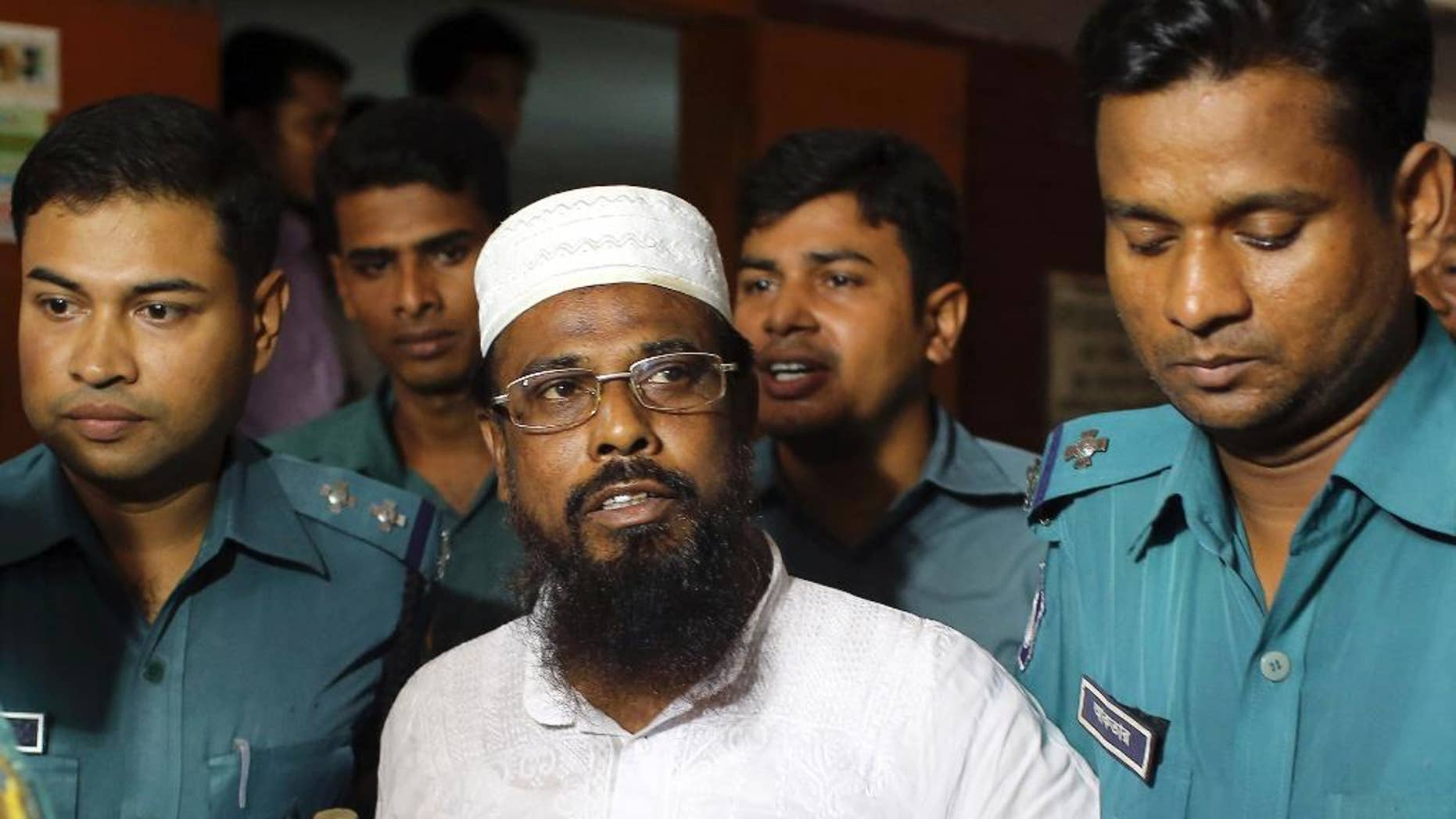 FILE - In this June 16, 2014 file photo, Mufti Abdul Hannan, center, leader of banned radical group Harkatul Jihad al Islami, stands at a court in Dhaka, Bangladesh. Bangladesh's Supreme Court on Sunday dismissed an appeal seeking the scrapping of a death sentence for the former head of a banned militant group over a 2004 grenade attack on Britain's then-envoy to Dhaka. (AP Photo/A.M. Ahad, File)