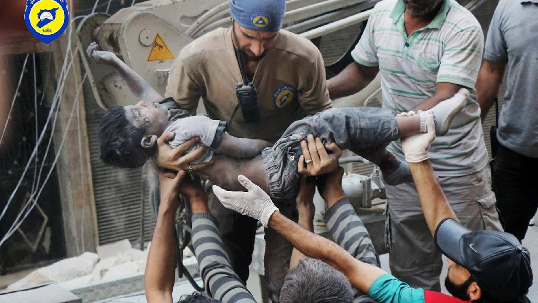 This Tuesday, Sept. 27, 2016 photo, provided by the Syrian Civil Defense group known as the White Helmets, shows a Civil Defense worker carrying the body of a child after airstrikes hit al-Shaar neighborhood in Aleppo, Syria. Pope Francis has decried the assault on the Syrian city of Aleppo, saying those responsible for the bombing must answer to God. (Syrian Civil Defense White Helmets via AP)