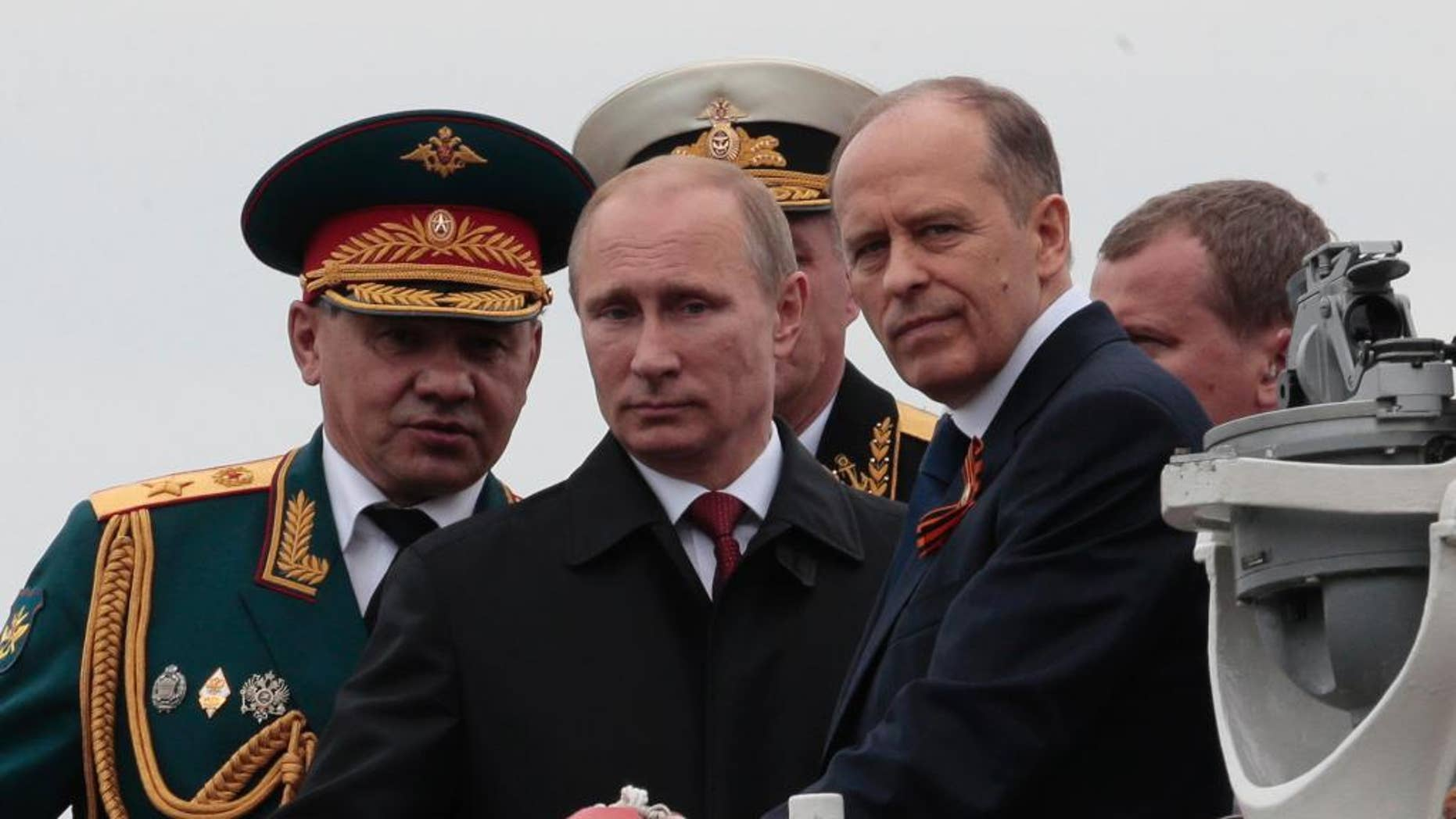 FILE - In this file photo taken on Friday, May 9, 2014, Russian President Vladimir Putin, centre, flanked by Defense Minister Sergei Shoigu, left, and Federal Security Service Chief Alexander Bortnikov, right, arrives on a boat after inspecting battleships during a navy parade marking the Victory Day in Sevastopol, Crimea. Putin on Thursday Aug. 11, 2016, directly accused the Ukrainian government of plotting attacks in the Crimea, and called for increased security in the Russian annexed Black Sea peninsula. (AP Photo/Ivan Sekretarev, FILE)
