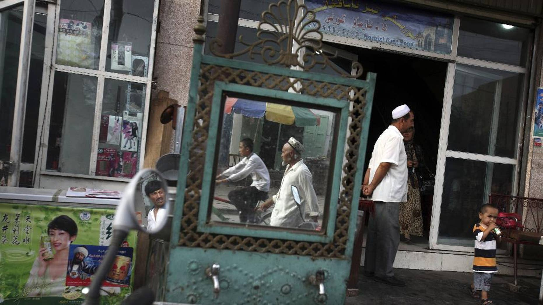 FILE -  In this Aug. 6, 2008, file photo, Uighurs are seen outside a restaurant in Kashgar in China's western Xinjiang province. Since 2015 militants belonging to the Uighur ethnic group native to the vast Xinjiang region in western China have shown signs of becoming a force in Islamic extremism globally, a development that is reshaping both the ground war in Syria and Chinese foreign policy. (AP Photo/Ng Han Guan, File)