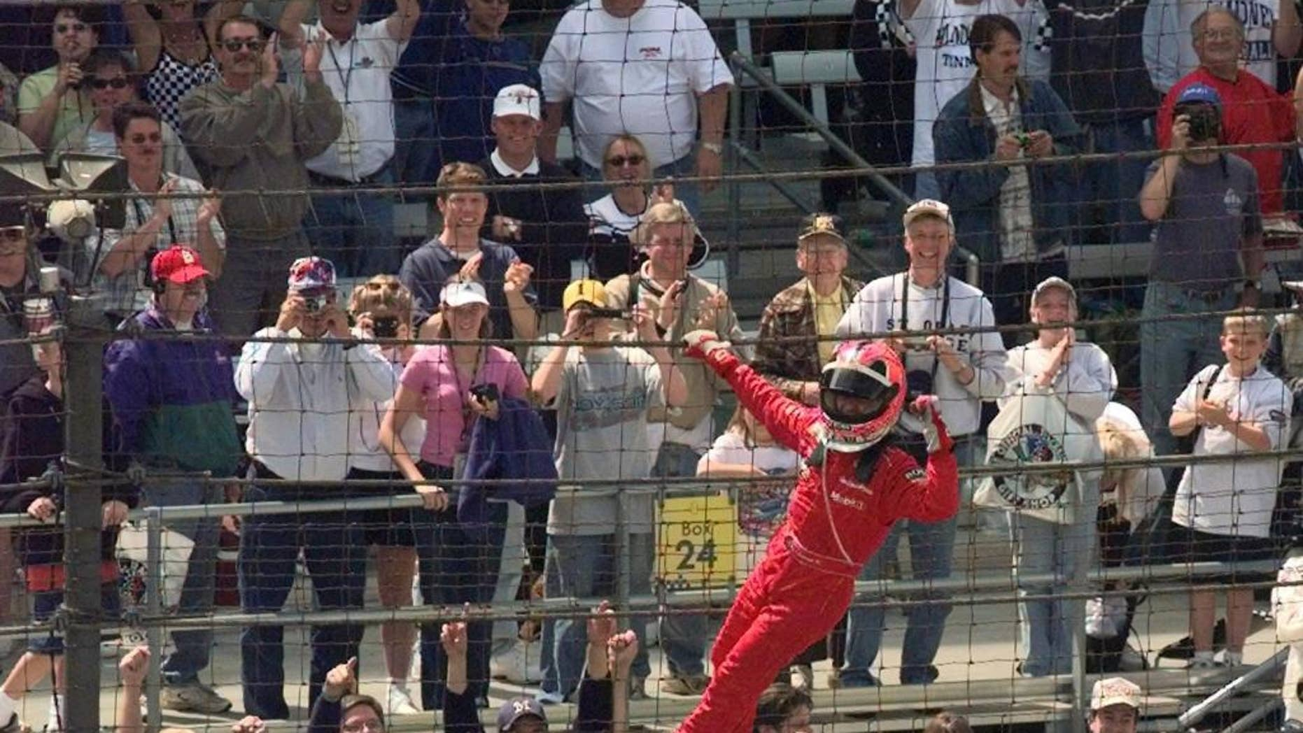 FILE - In this May 27, 2001, file photo, Helio Castroneves, of Brazil, celebrates after winning the 85th running of the Indianapolis 500 auto race by climbing the fencing near the start-finish line at Indianapolis Motor Speedway. (AP Photo/Dave Parker, File)
