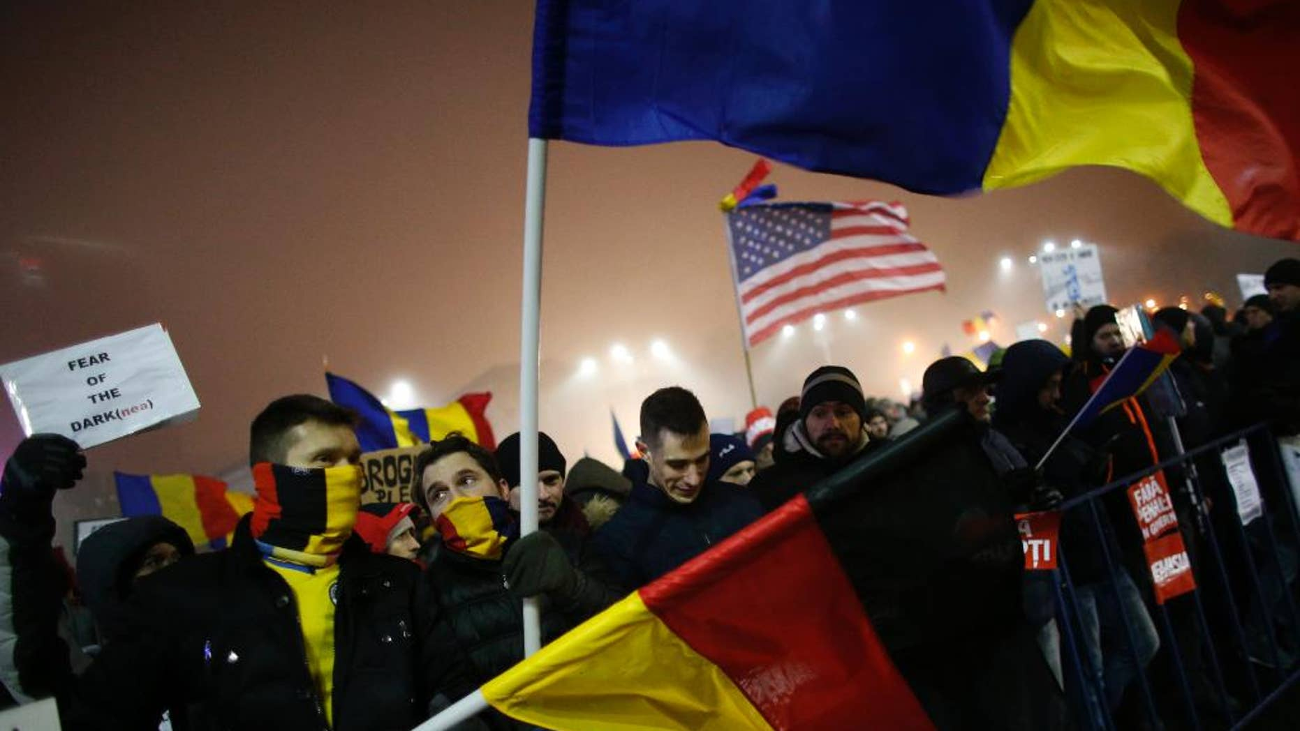 Protesters wave U.S., German and Romanian flags during a protest in Bucharest, Romania, Monday, Feb. 6, 2017. The leader of Romania's ruling center-left coalition said Monday the government won't resign following the biggest demonstrations since the end of communism against a measure that would ease up on corruption. (AP Photo/Darko Bandic)