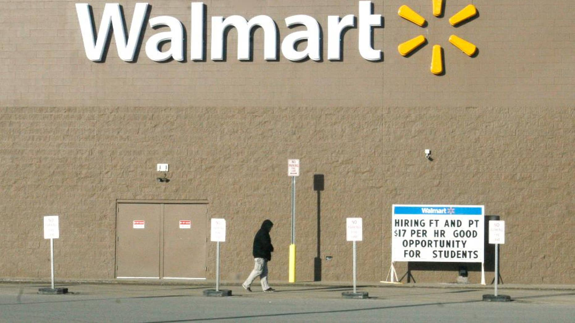 ADVANCE FOR USE SUNDAY, APRIL 13, 2014 AND THEREAFTER - A shopper walks next to a Walmart store on Friday, Feb. 28, 2014 in Williston, N.D. near a sign advertising a $17 hourly wage for new employees - a rate higher than in many cities. The Bakken shale fields oil boom has brought about a high cost of living in the area, especially for housing. (AP Photo/Martha Irvine)