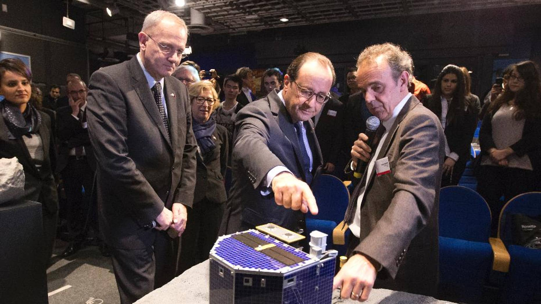 FILE - In this Wednesday, Nov. 12, 2014 file photo, French President Francois Hollande, center, with French astrophysicist Francis Rocard look at a model of Rosetta lander Philae, as they visit the Cite des Sciences at La Villette in Paris during a broadcast of the Rosetta mission as it orbits around comet 67/P Churyumov-Gersimenko. The European Space Agency says Wednesday July 27, 20167  it is switching off its radio link to the probe that landed on a comet, after receiving no signal from the lander for a year.  (AP Photo/Jacques Brinon, Pool, file)