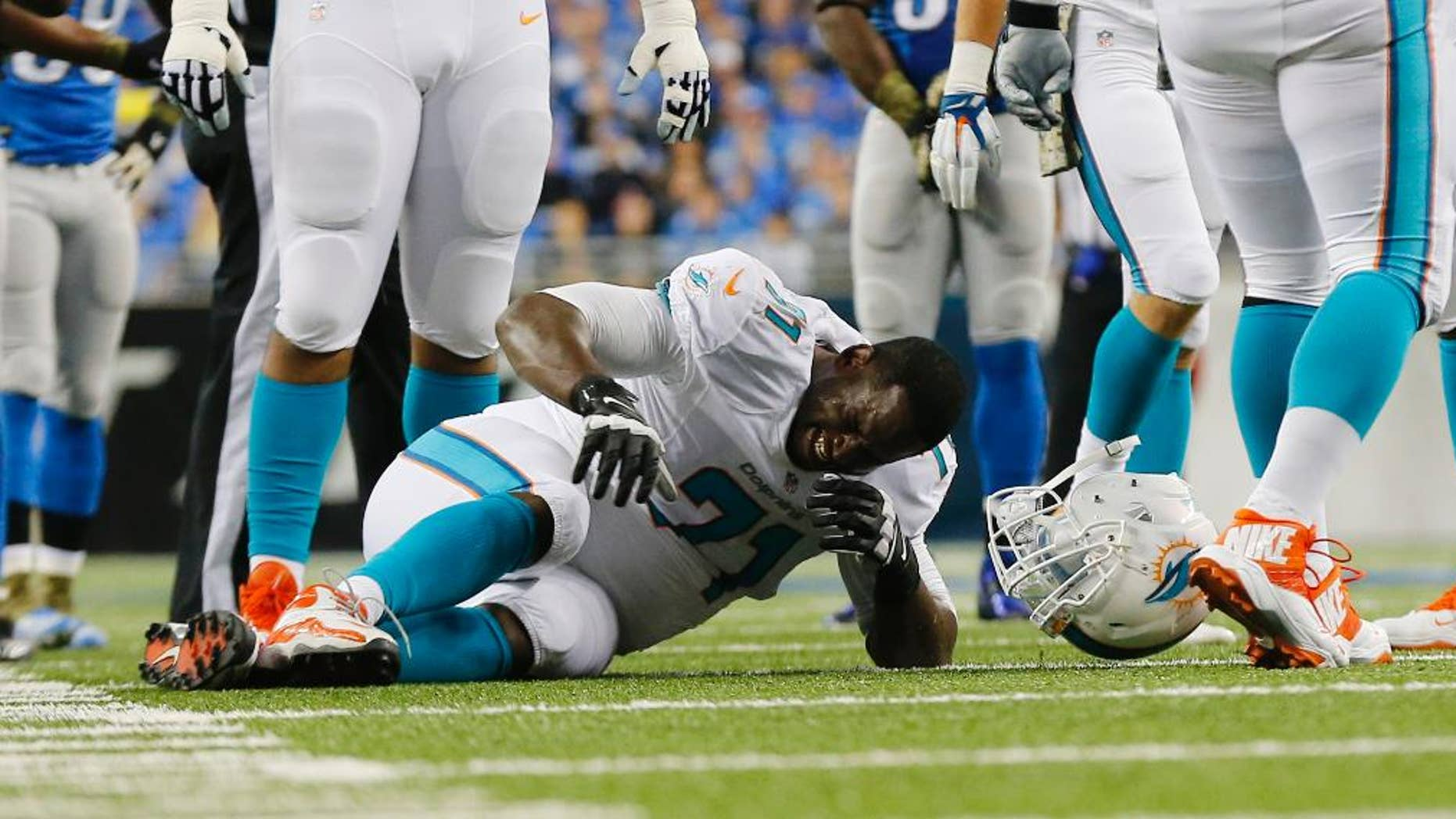 Miami Dolphins tackle Branden Albert (71) grimaces during the first half of an NFL football game against the Detroit Lions in Detroit, Sunday, Nov. 9, 2014. Albert was carted off the field. (AP Photo/Paul Sancya)
