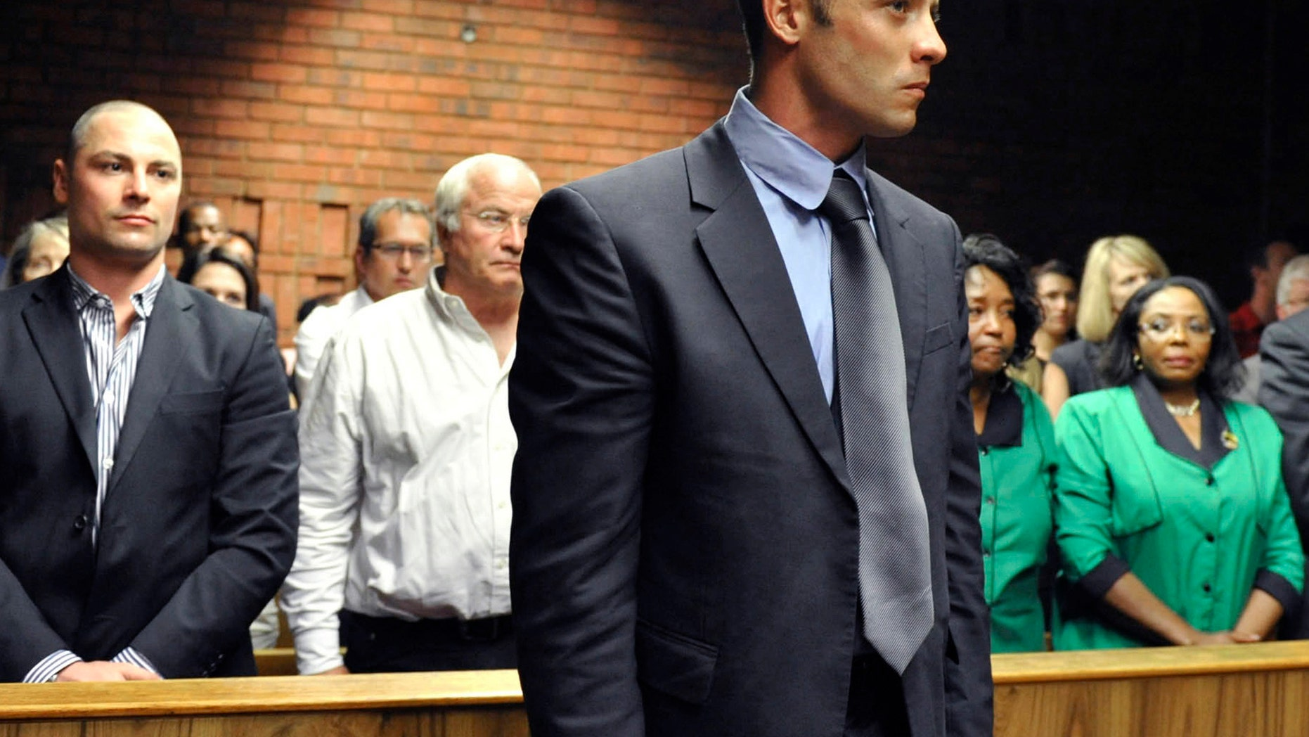 Olympian Oscar Pistorius, foreground, stands following his bail hearing, as his brother Carl, left, and father Henke, second from left, look on in Pretoria, South Africa, Tuesday, Feb. 19, 2013. Pistorius fired into the door of a small bathroom where his girlfriend was cowering after a shouting match on Valentine's Day, hitting her three times, a South African prosecutor said Tuesday as he charged the sports icon with premeditated murder. The magistrate ruled that Pistorius faces the harshest bail requirements available in South African law. He did not elaborate before a break was called in the session. (AP Photo)