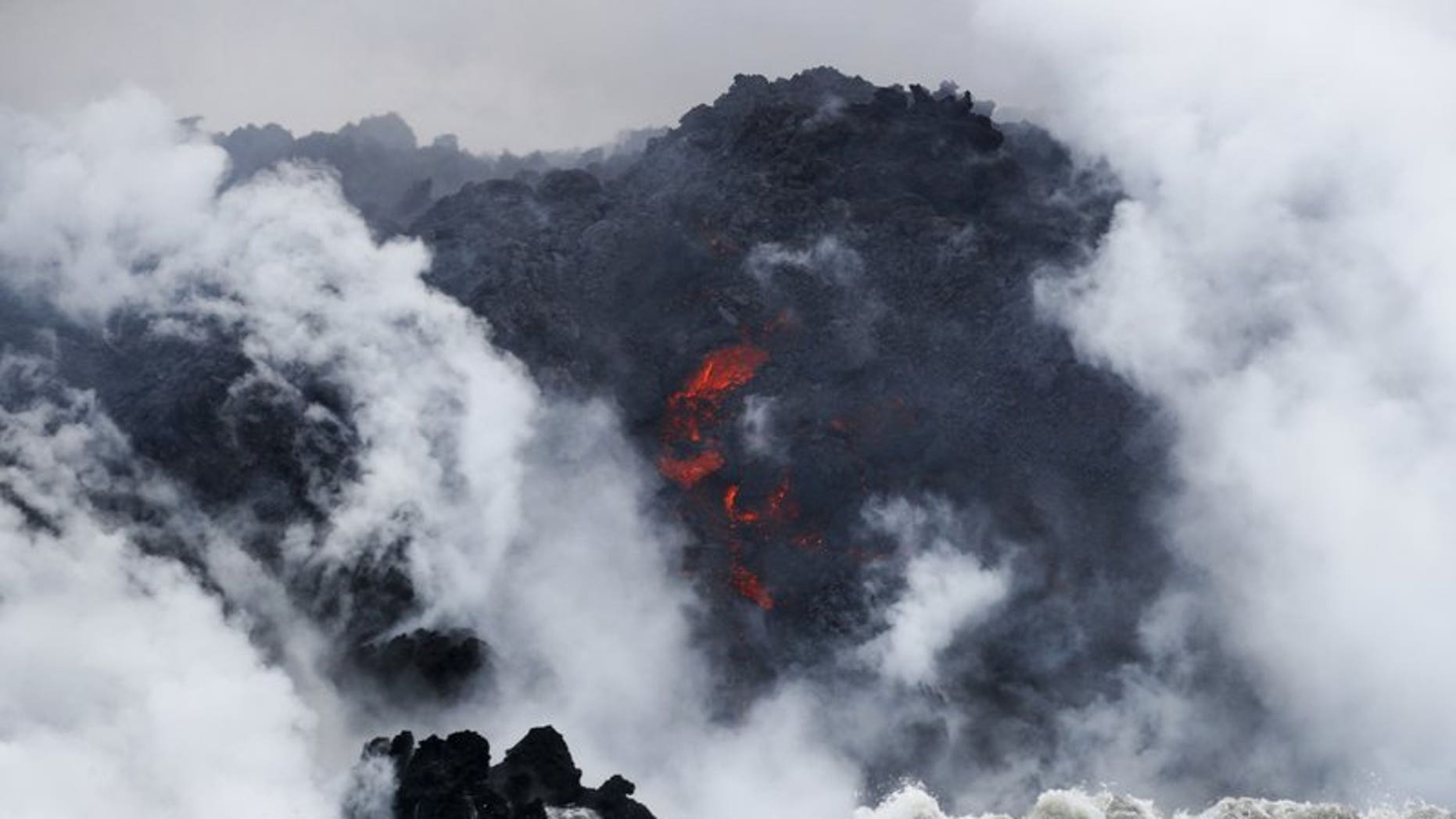 FILE: Lava flows into the ocean near Pahoa, Hawaii. Officials say an explosion sent lava flying through the roof of a tour boat.