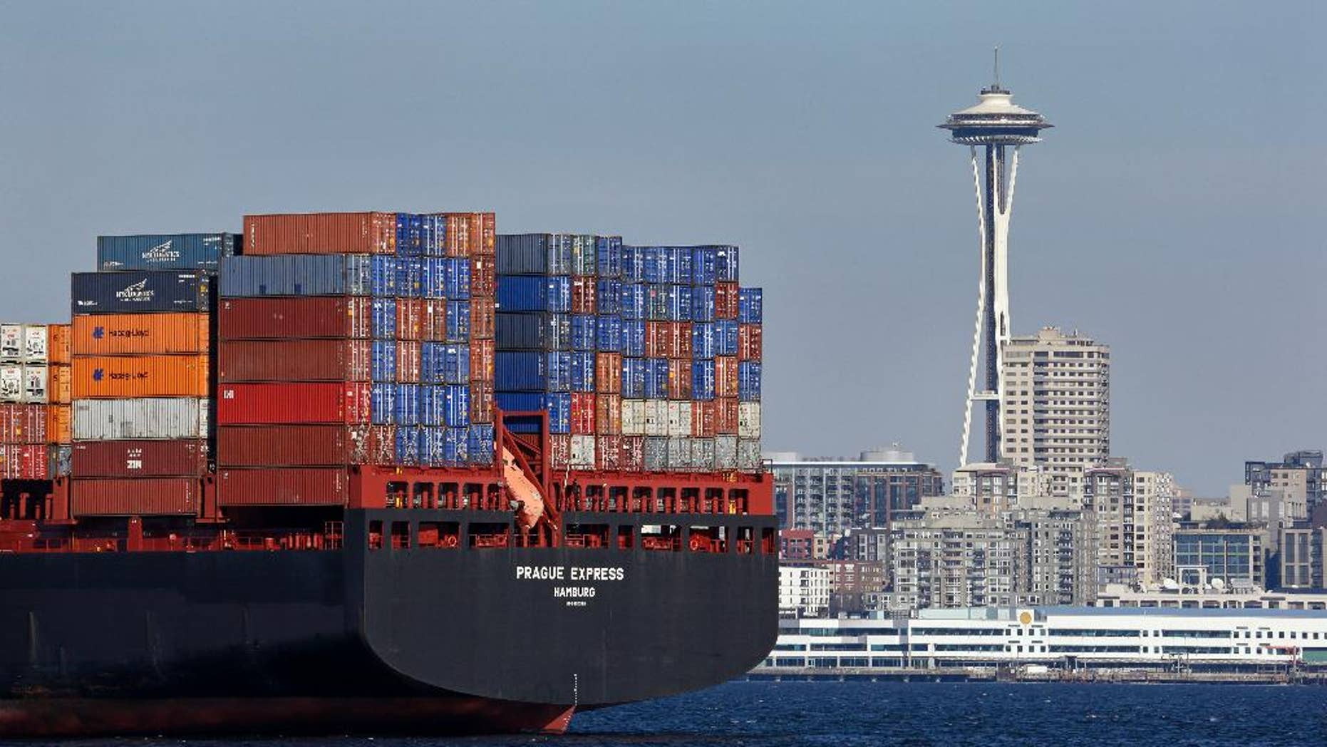 FILE - In this Feb. 15, 2015 file photo, the Space Needle towers in the background beyond a container ship anchored in Elliott Bay near downtown Seattle. The Commerce Department releases international trade data for January on Friday, March 6, 2015. (AP Photo/Elaine Thompson, File)