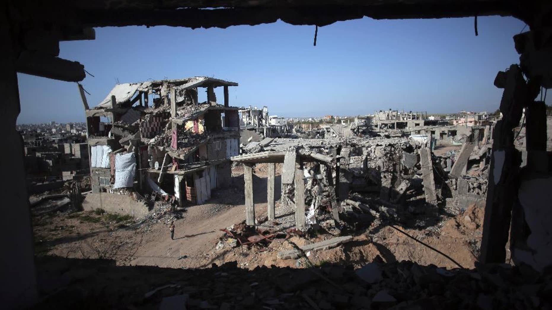 "File - In this March 30, 2015 file photo, a Palestinian girl walks next to destroyed houses, in the Shijaiyah neighborhood of Gaza City. The International Monetary Fund said in a Tuesday, May, 19, 2015 report, that reconstruction of the Gaza Strip is going ""far more slowly than expected"" after a devastating war between Israel and the Hamas militant group last year. The IMF said that just over a quarter of $3.5 billion pledged for reconstruction has been disbursed and urged donors to fulfill their pledges.  (AP Photo/Khalil Hamra, File)"