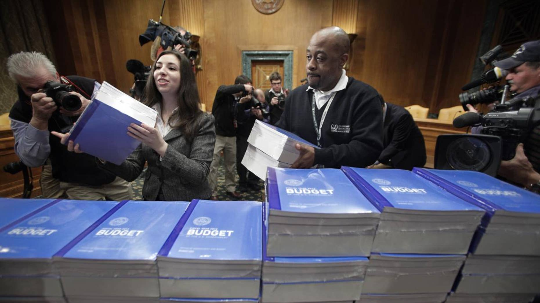 Copies of President Obama's 2012 budget are delivered to the Senate Budget Committee, Monday, Feb. 14, 2011, on Capitol Hill in Washington. (AP Photo/J. Scott Applewhite)