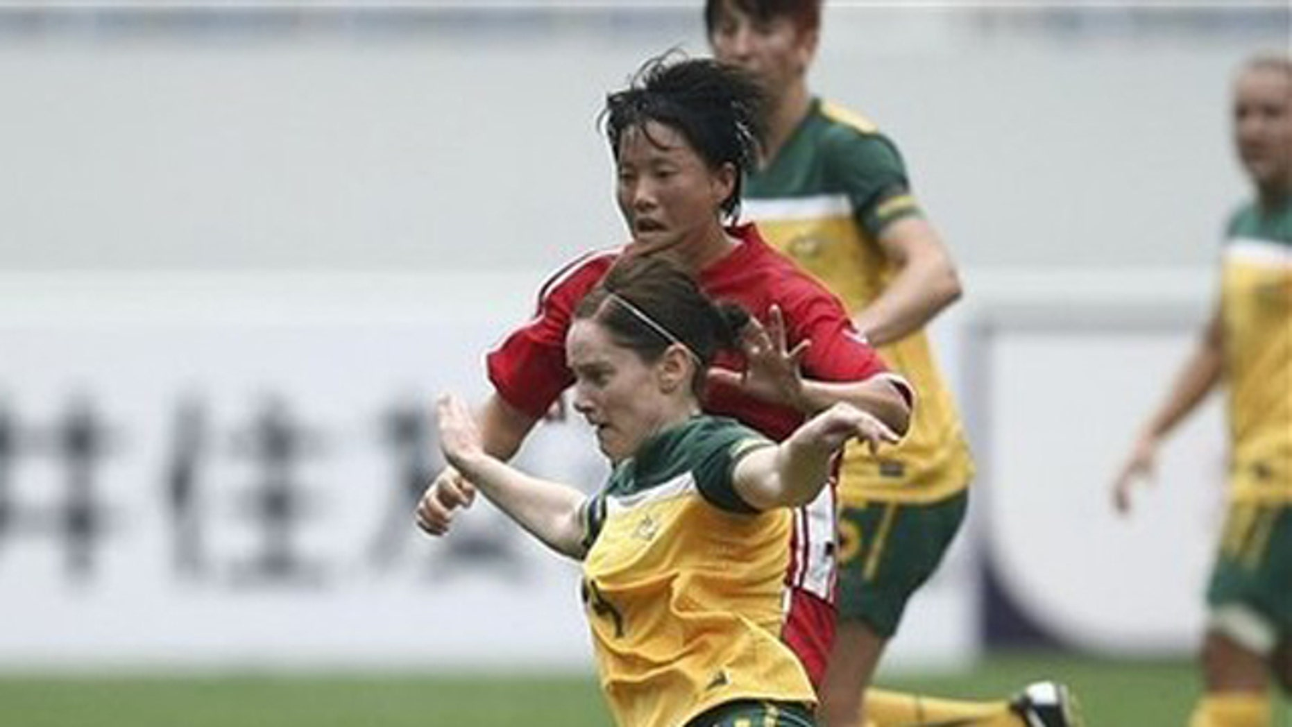 Sept. 1, 2011: Australian Collette McCallum, foreground, and Ri Ye Gyong of North Korea wrestle for the ball during their women's qualifying soccer tournament for the 2012 Olympic Games in Jinan, China.