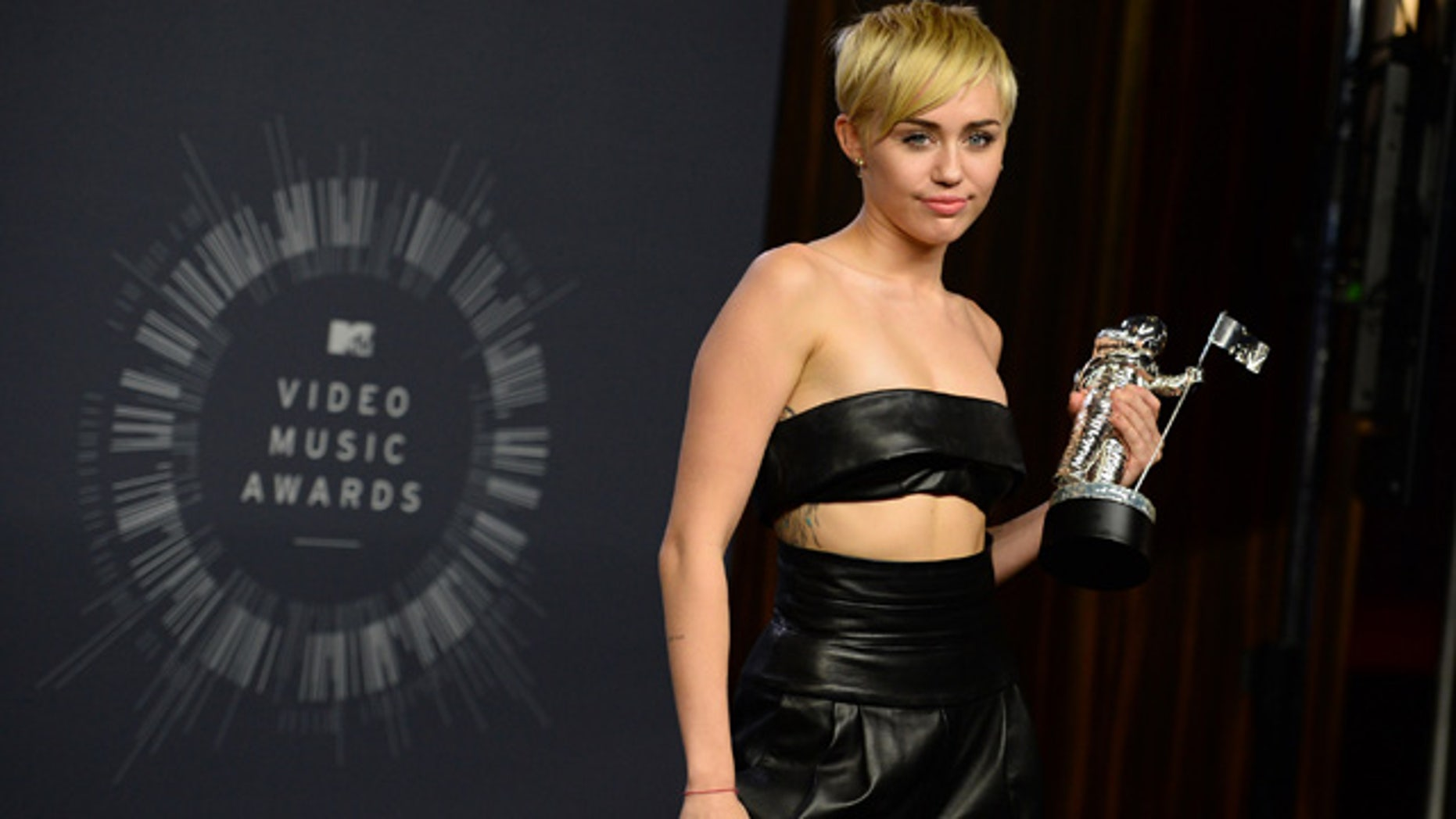 August 24, 2014: Miley Cyrus poses with the award for Video of the Year in the press room at the MTV Video Music Awards at The Forum in Inglewood, Calif. (Photo by Jordan Strauss/Invision/AP)