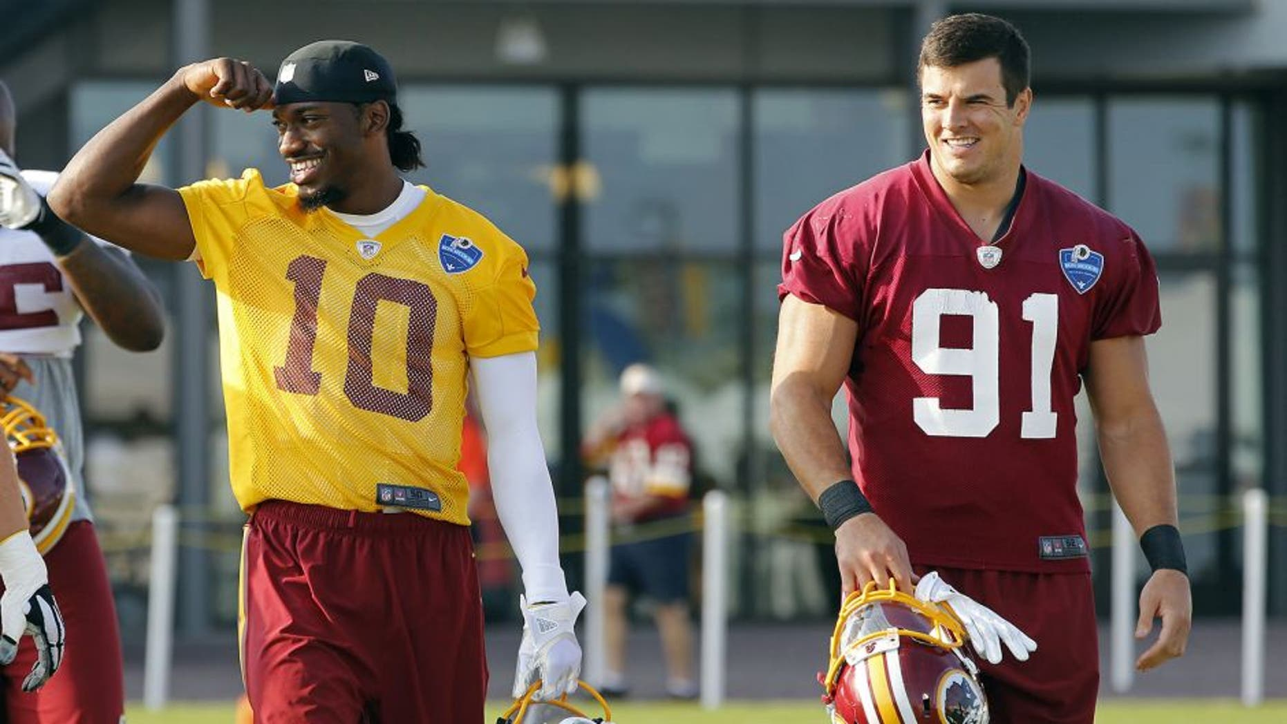Aug 6, 2014; Richmond, VA, USA; Washington Redskins quarterback Robert Griffin III (10) and outside linebacker Ryan Kerrigan (91) walk onto the field prior to joint practice with the New England Patriots on day twelve at the Bon Secours Washington Redskins Training Center. Mandatory Credit: Geoff Burke-USA TODAY Sports