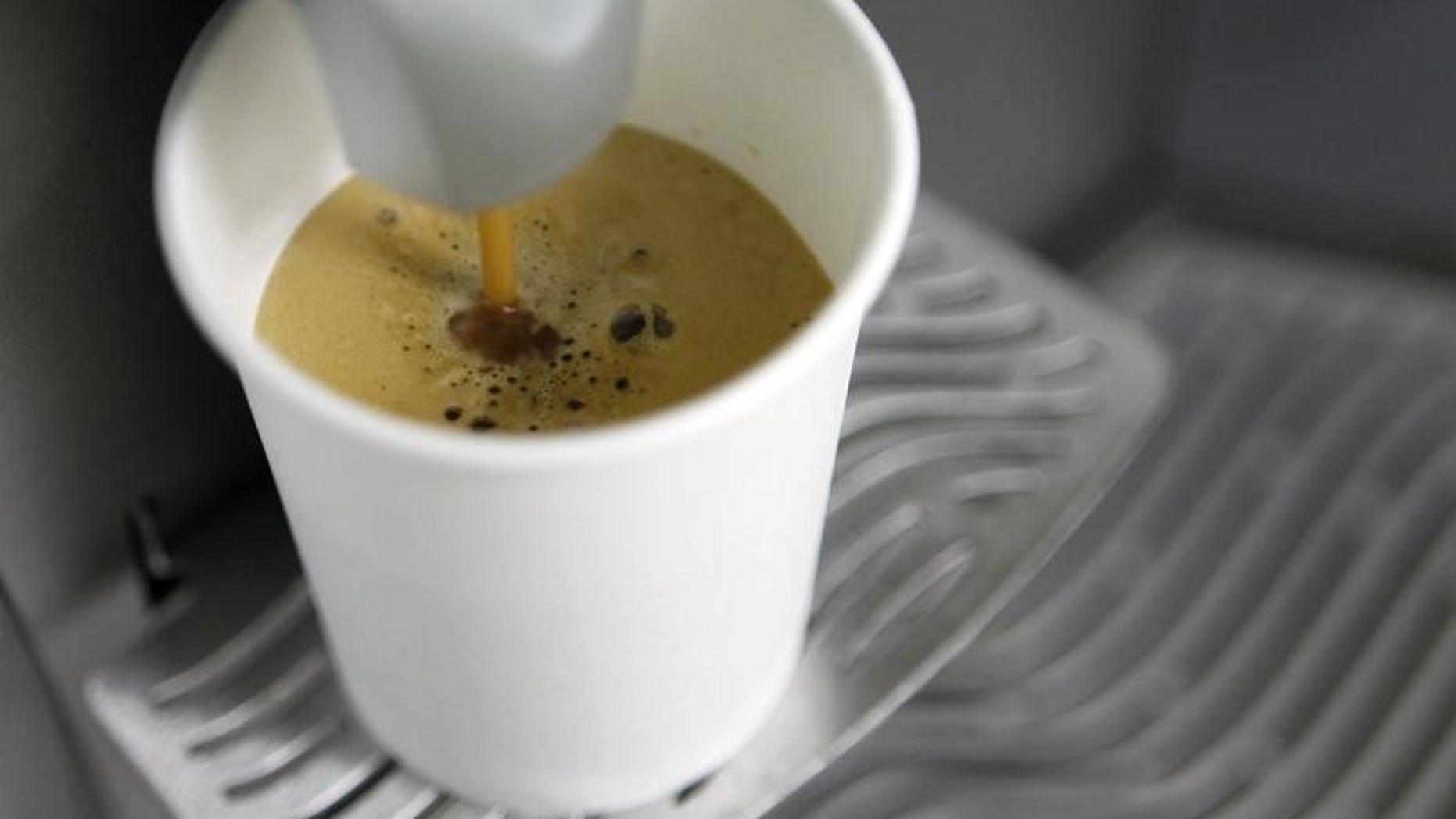 A coffee machine pours coffee into a paper cup in Kiev March 1, 2012.   REUTERS/Gleb Garanich