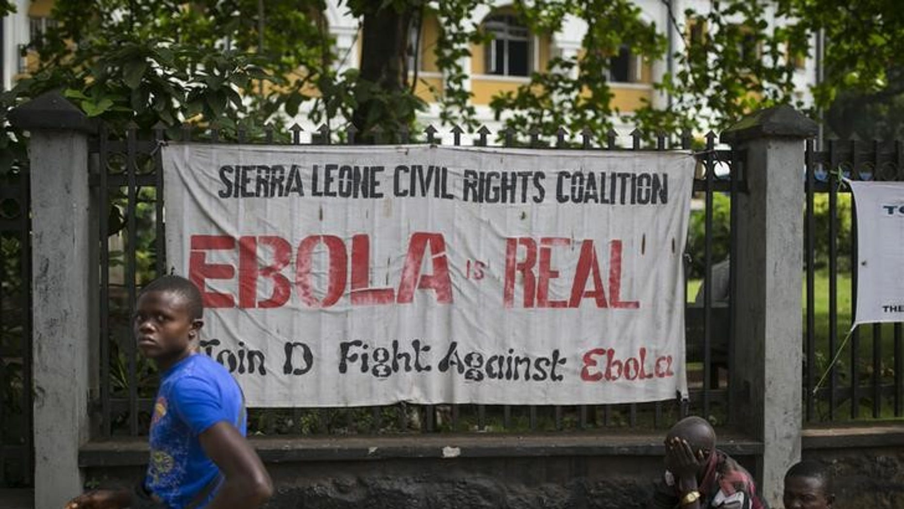 A man walks past a banner about Ebola in Freetown, Sierra Leone, December 16, 2014.