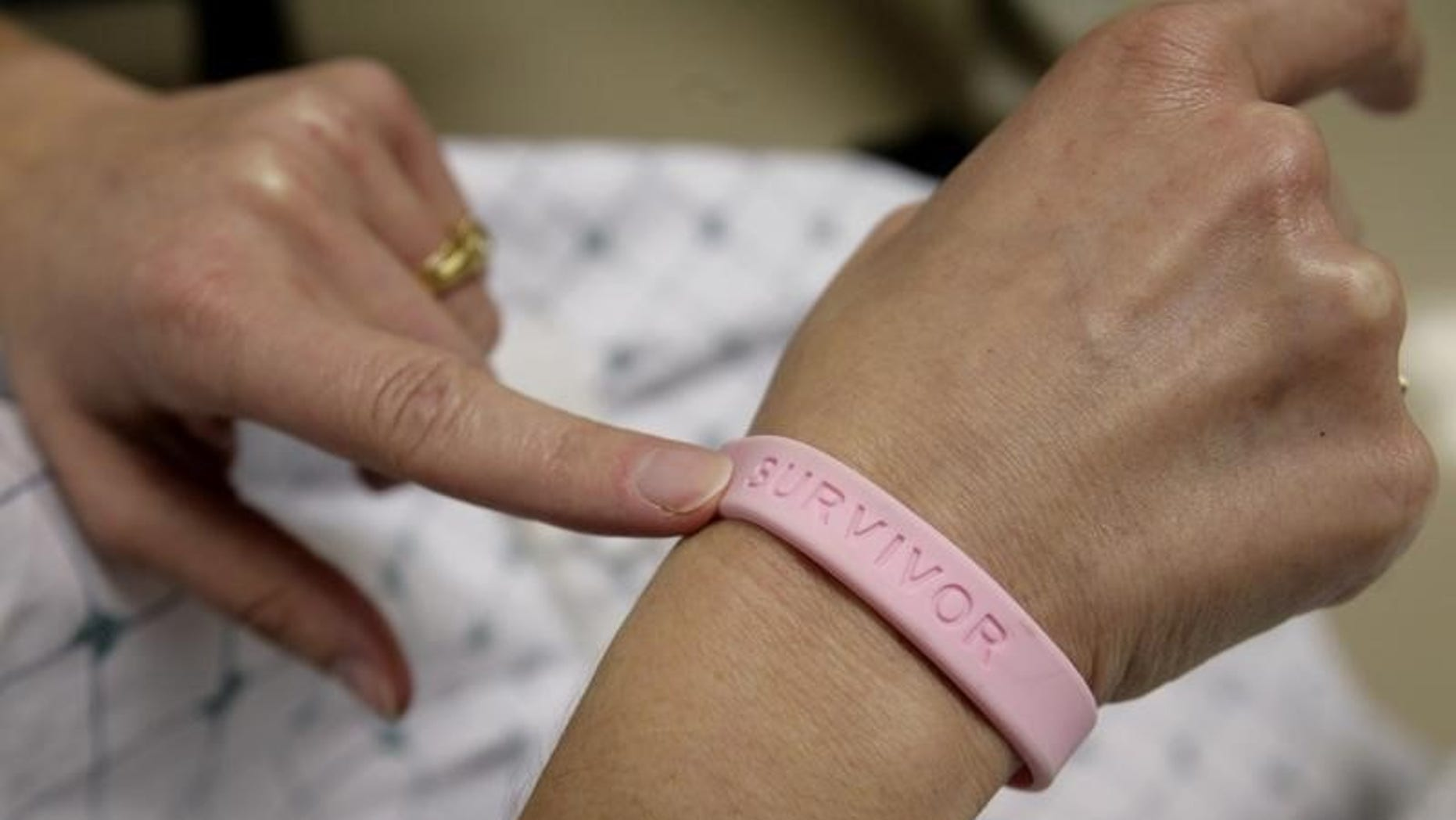 After three operations and four rounds of chemotherapy at Georgetown University Hospital, cancer patient Deborah Charles shows off her breast cancer survivor bracelet during a hospital appointment in Washington May 23, 2007. REUTERS/Jim Bourg