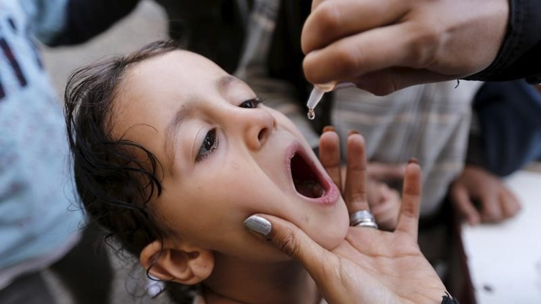 A girl receives polio vaccine drops at a school in Sanaa sheltering people after conflict forced them to flee their homes in Yemen's Houthi-controlled northern province of Saada August 15, 2015. REUTERS/Khaled Abdullah