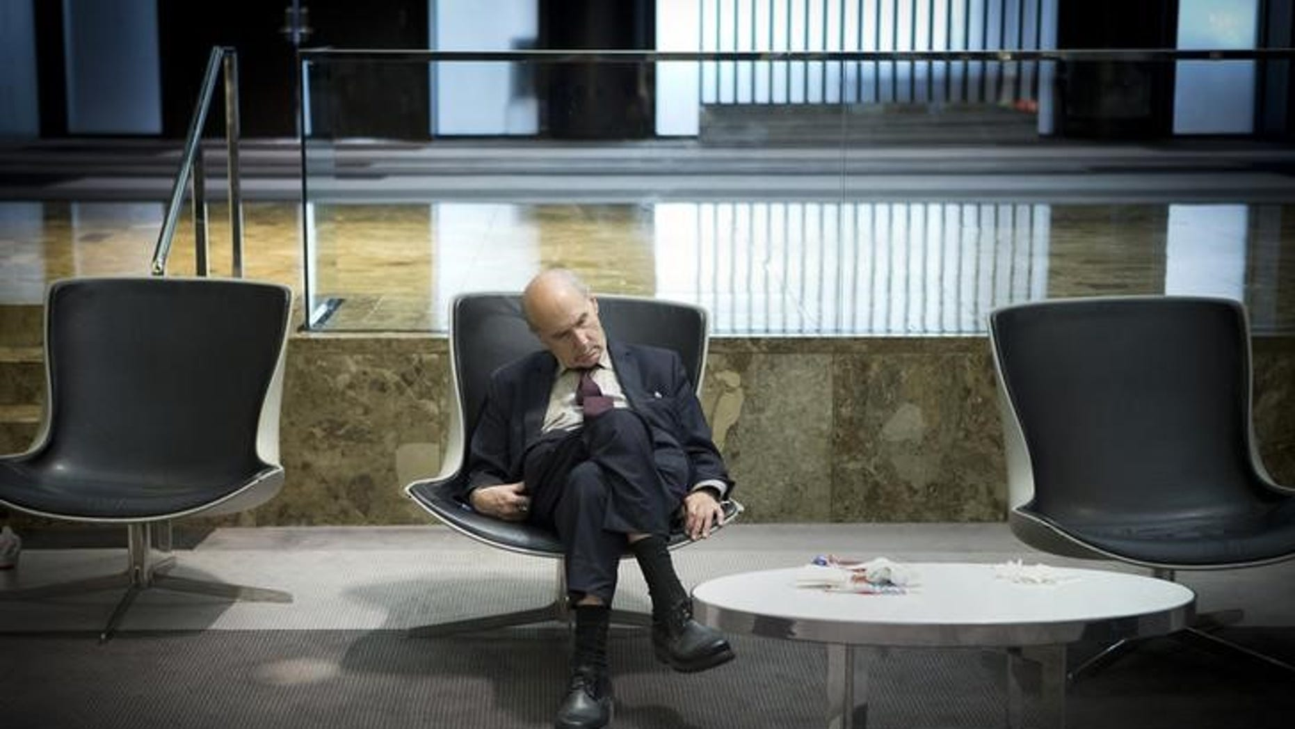 A businessman takes a mid-day nap in the lobby of a midtown hotel in the Manhattan borough of New York August 1, 2014.      REUTERS/Carlo Allegri