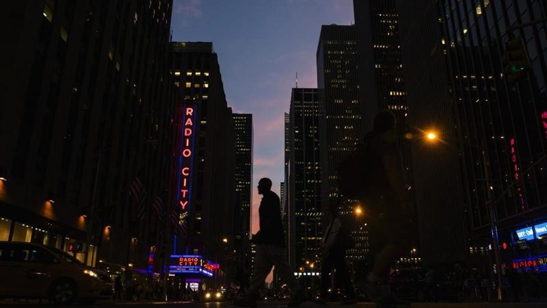 A man crosses 6th Avenue as the sun sets in New York September 3, 2014. REUTERS/Lucas Jackson
