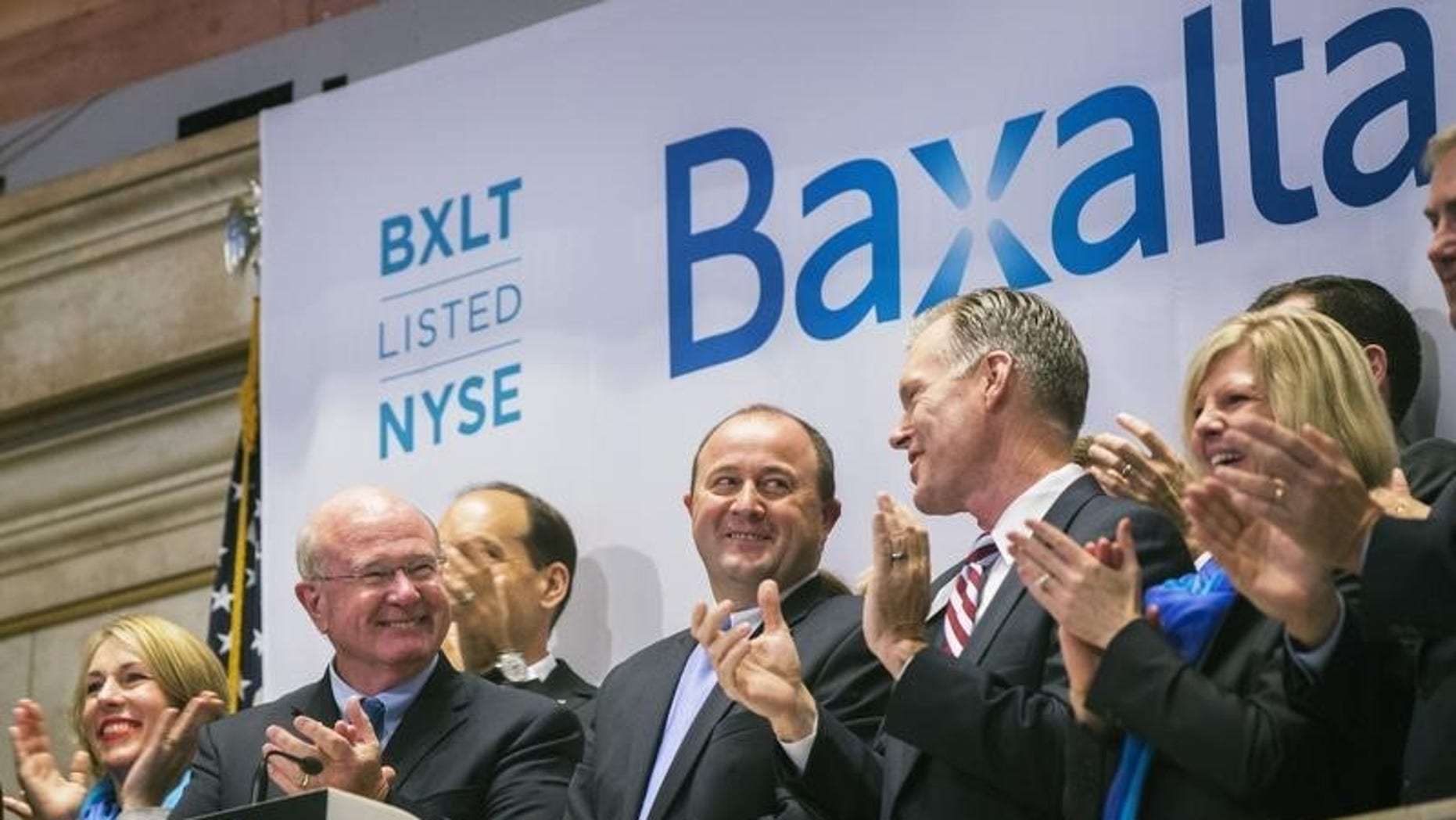 Ludwig Hantson (C), Chief Executive Officer of Baxalta, celebrates the company's IPO after ringing the opening bell above the floor of the New York Stock Exchange, July 1, 2015. REUTERS/Lucas Jackson