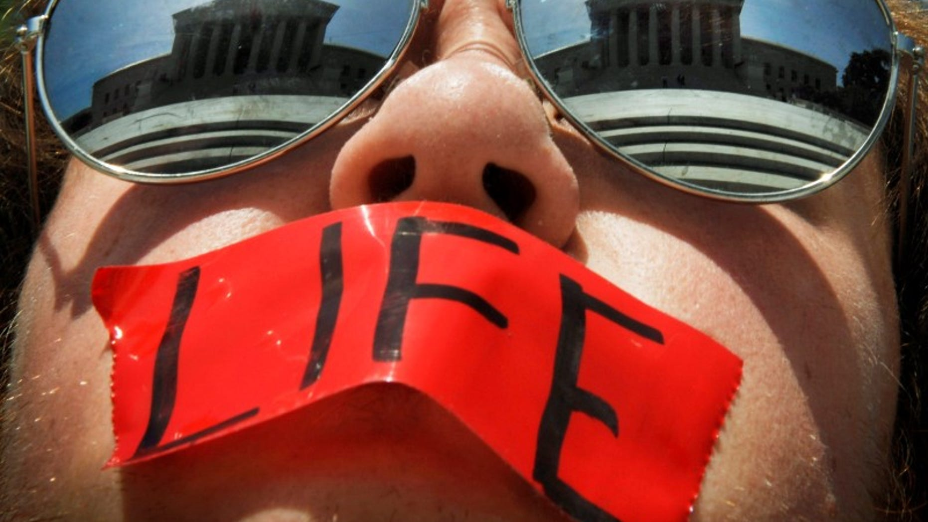 Anti-abortion activist Craig Kuhns wears mirrored sunglasses and a piece of tape over his mouth as he stands in front of the US Supreme Court building in Washington, in this June 1, 2009 file photo.REUTERS/Jonathan Ernst/Files