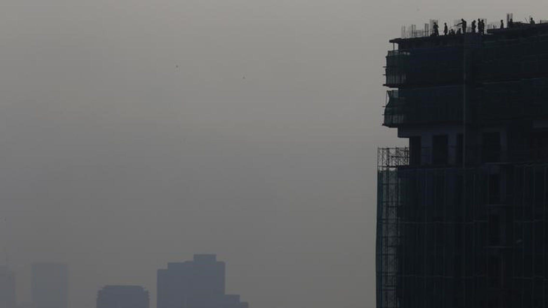 Builders work on hazy day in Kuala Lumpur, Malaysia, October 8, 2015. REUTERS/Olivia Harris