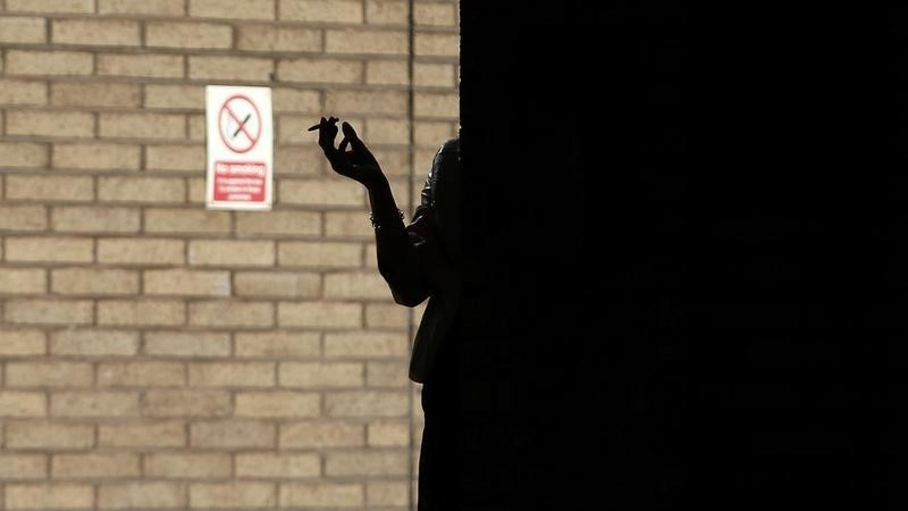 A woman smokes in the shadows outside Southwark Crown Court in central London, March 5, 2014. REUTERS/Andrew Winning