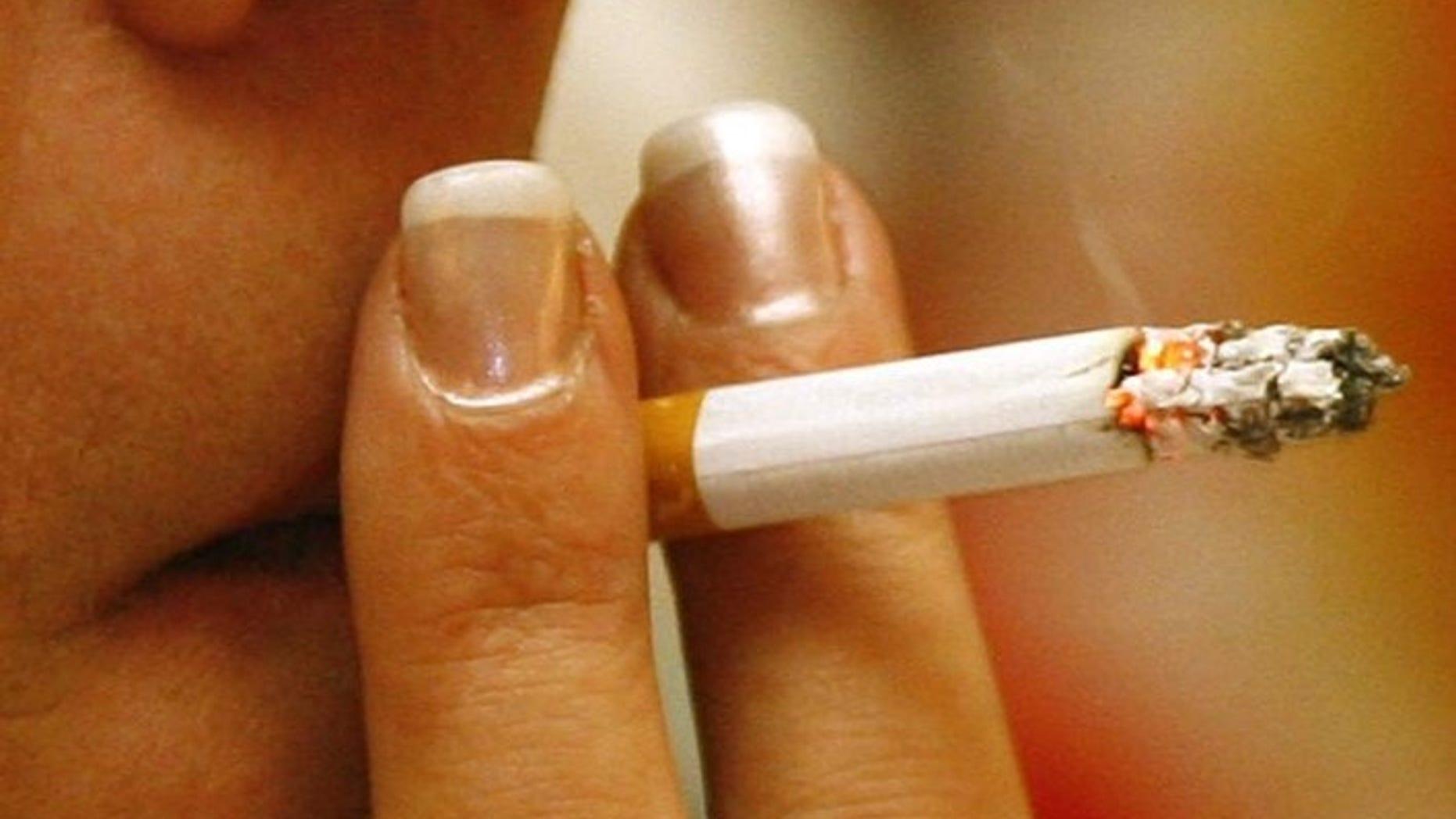 A woman smokes a cigarette in a restaurant in Munich, December 31, 2007.  REUTERS/Alexandra Beier